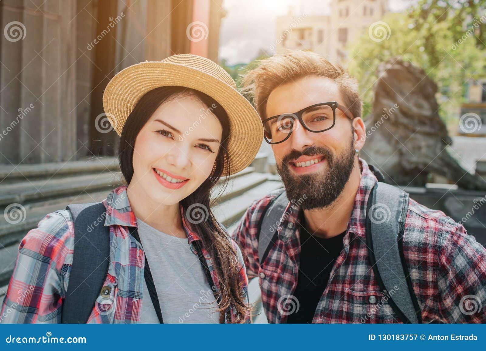 Славное изображение 2 молодых туристов смотря на камере и усмехаться Снаружи стойки человека и женщины близко к лестницам Они име