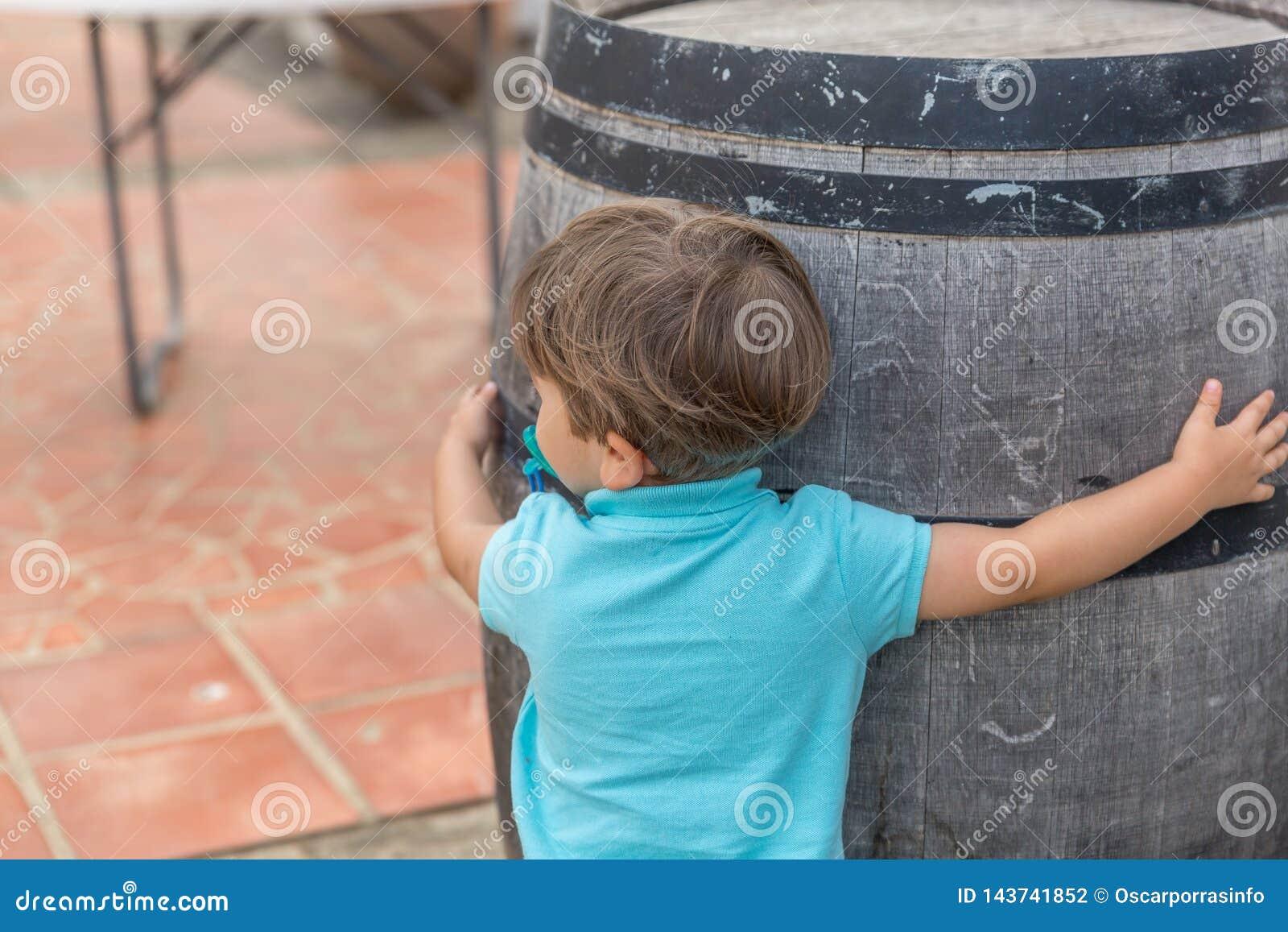 Славный мальчик одетый в сини с объятиями pacifier бочонок