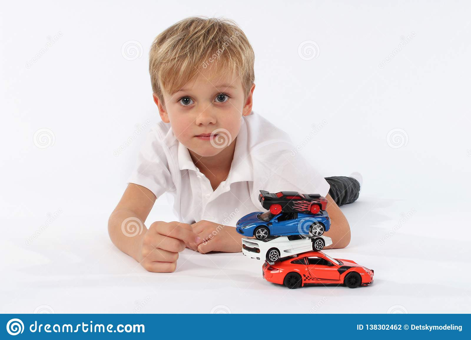 Славный смотрящ очень молодого мальчика лежа с кучей игрушек автомобиля и имея задушевную нейтраль и гордый взгляд в его стороне