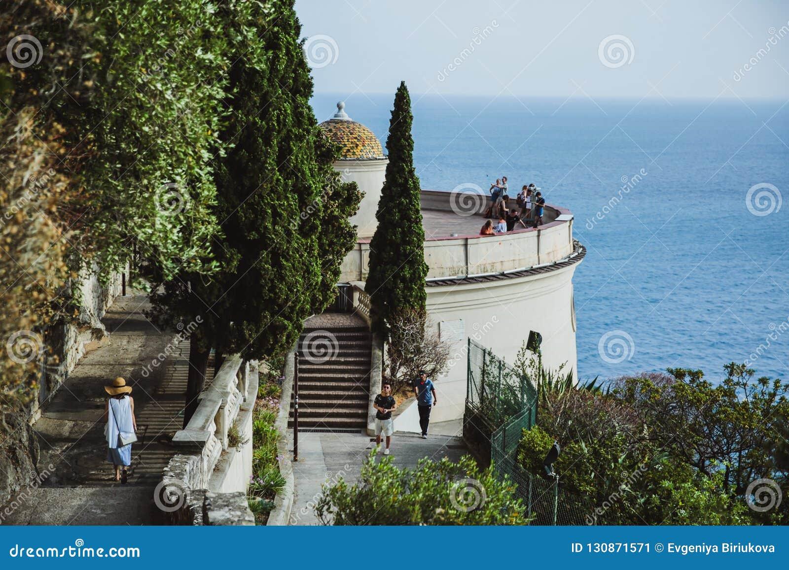 СЛАВНЫЙ, ФРАНЦИЯ - 26-ОЕ ИЮНЯ 2017: Женщина идет вниз с лестниц в смотровую площадку в холме замка или парк Colline du Замка в сл