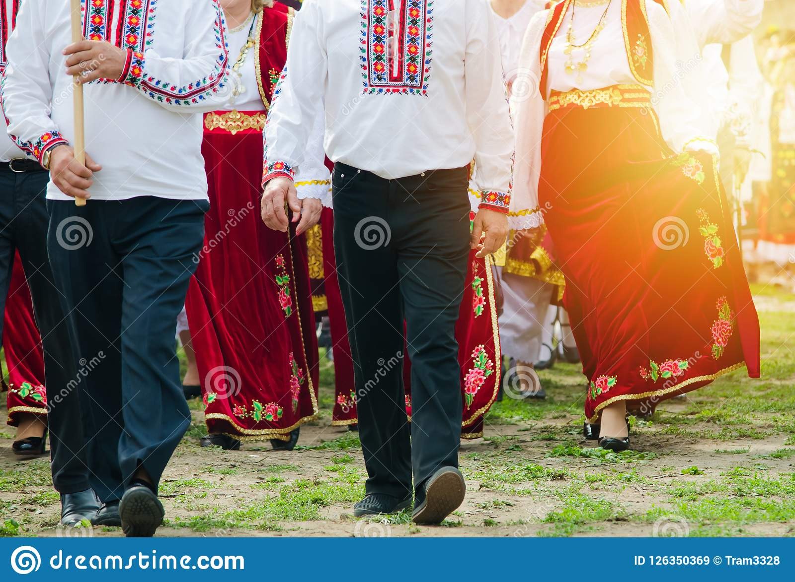 Славянские люди и женщины в традиционных костюмах outdoors
