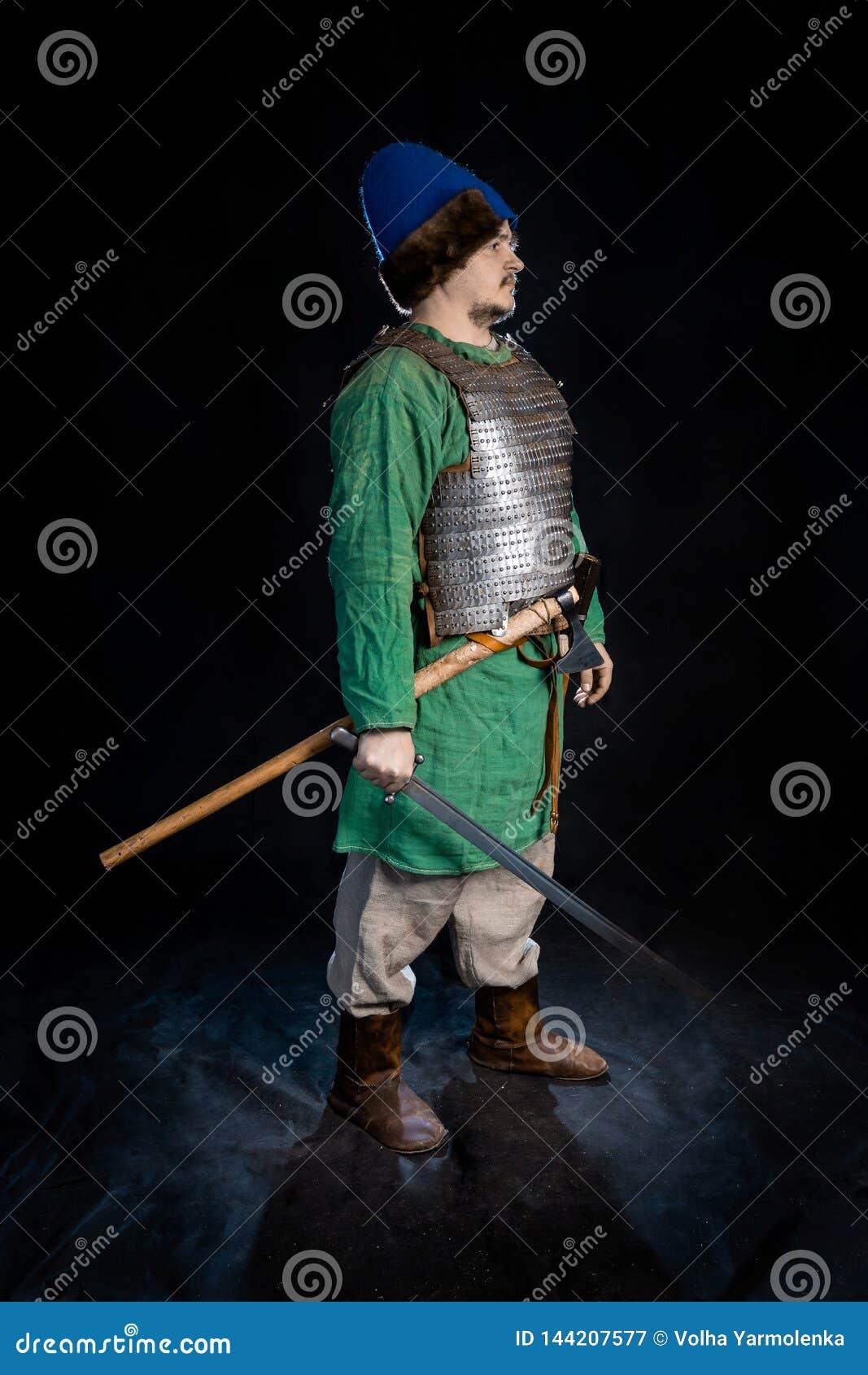 Славянский воин возраста Викинга в панцыре и винтажной шляпе со шпагой и осью