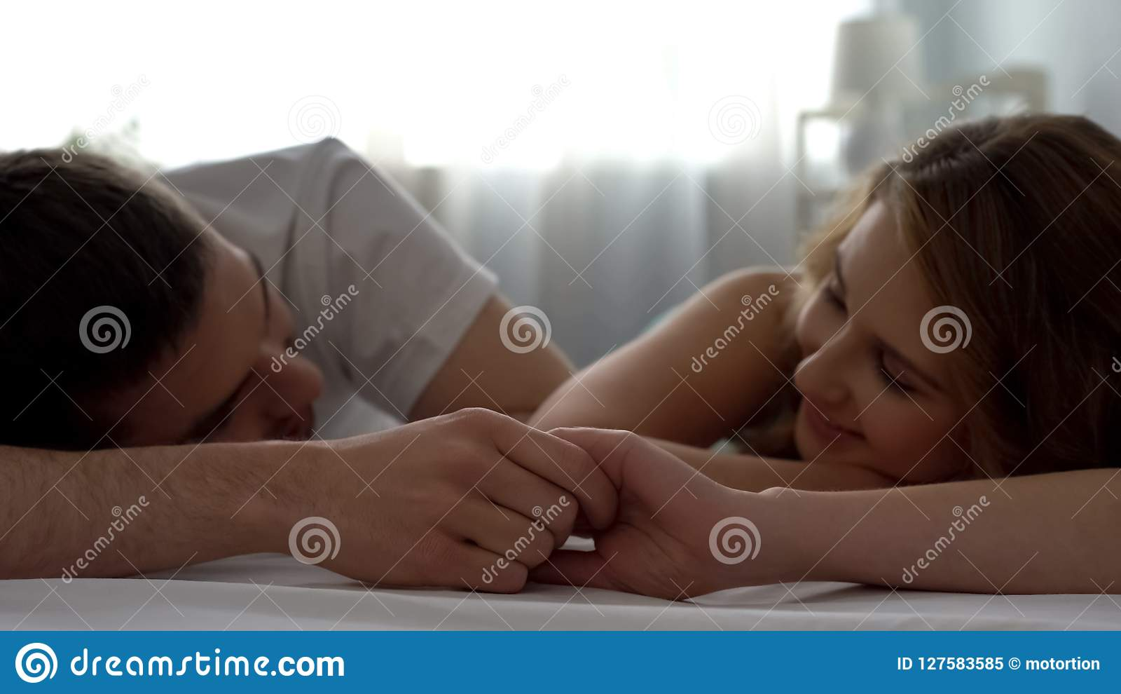 Сладостные пары смотря один другого при влюбленность, держа руки в кровати, сомкнутость