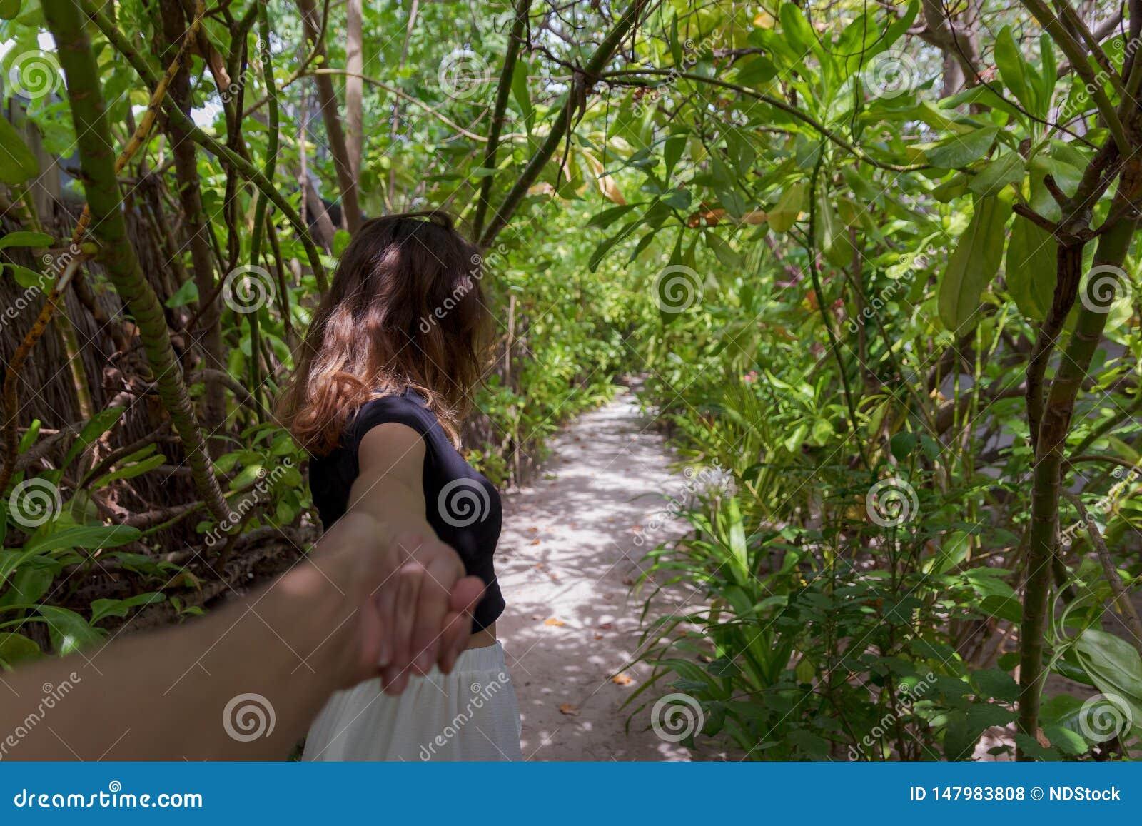 Следовать мной концепция молодой женщины идя на путь окруженный зеленой растительностью