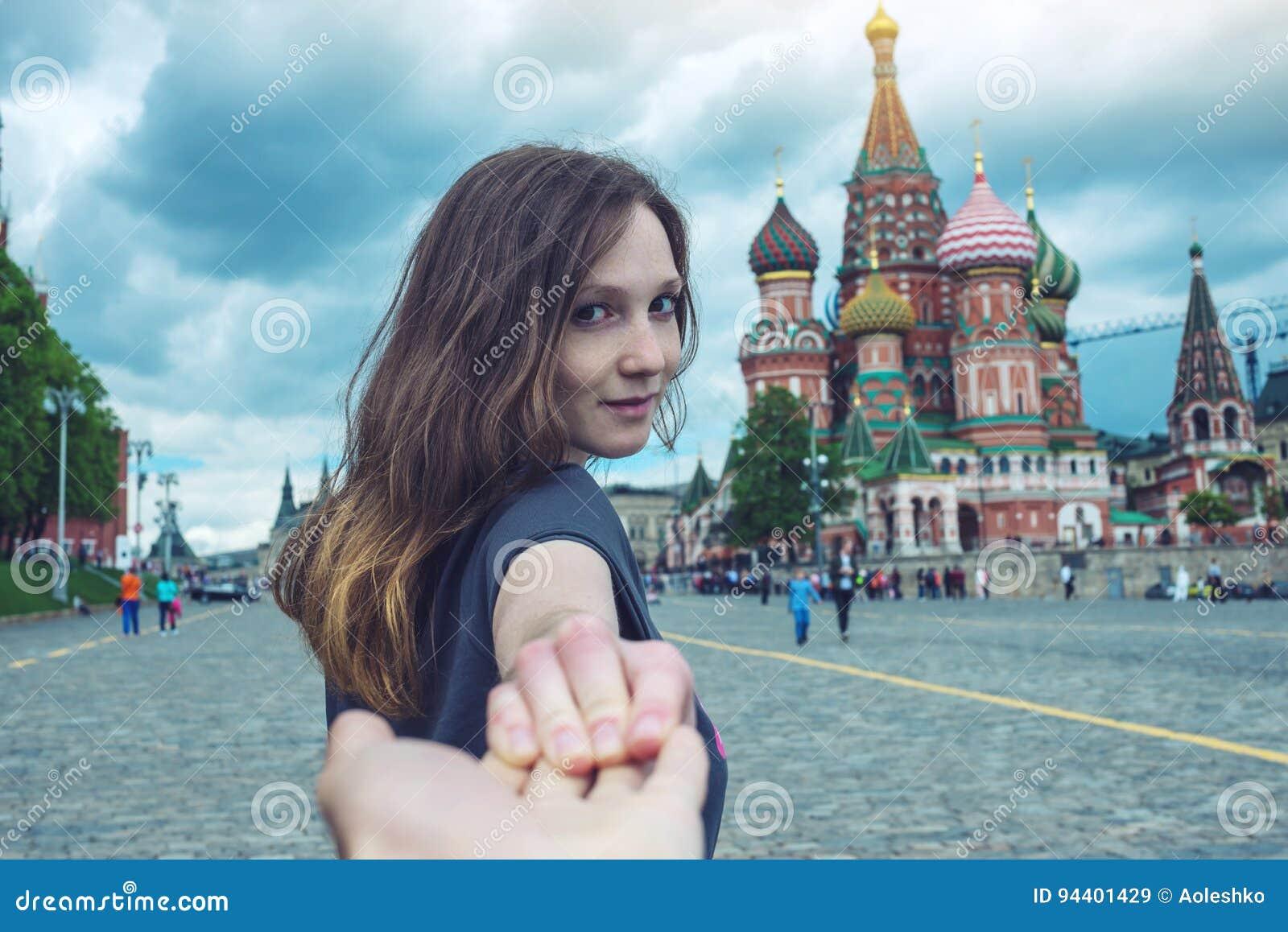 Следовать мной, привлекательным брюнет девушка держа руку водит к красной площади в Москве Россия