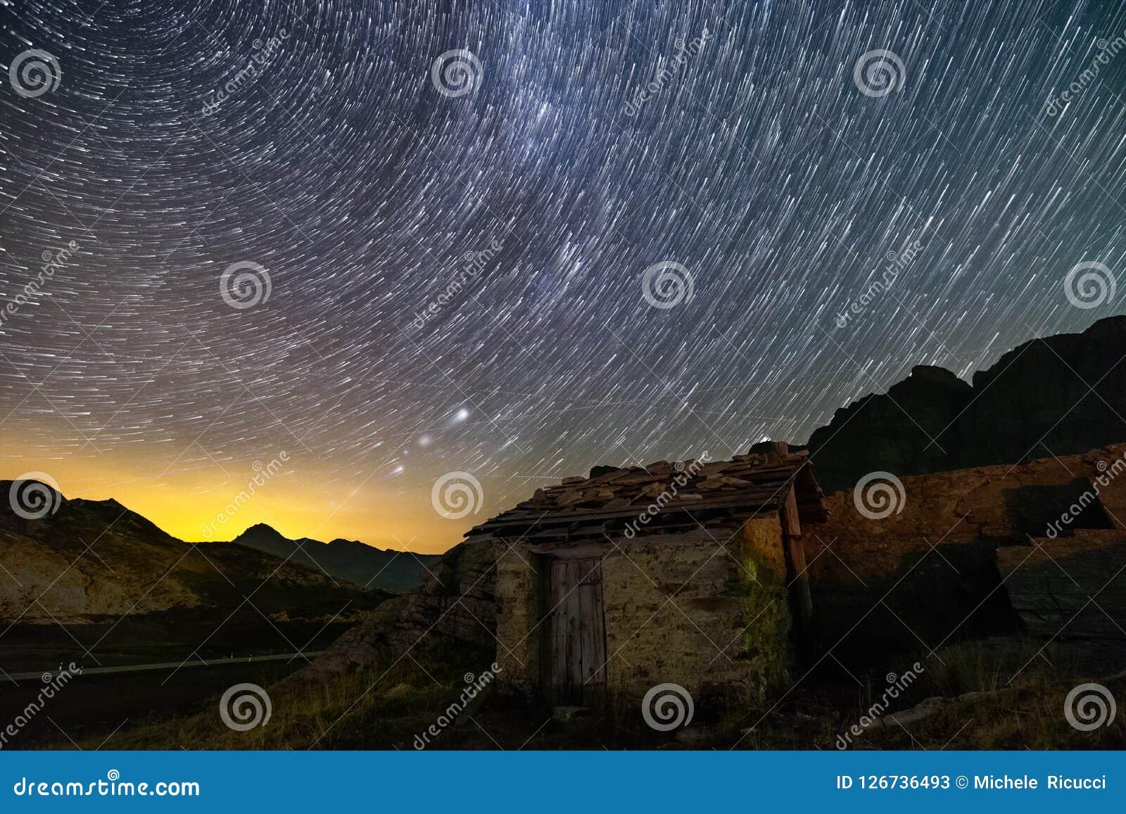 Следы звезд и изолированный дом в горных вершинах Швейцарии