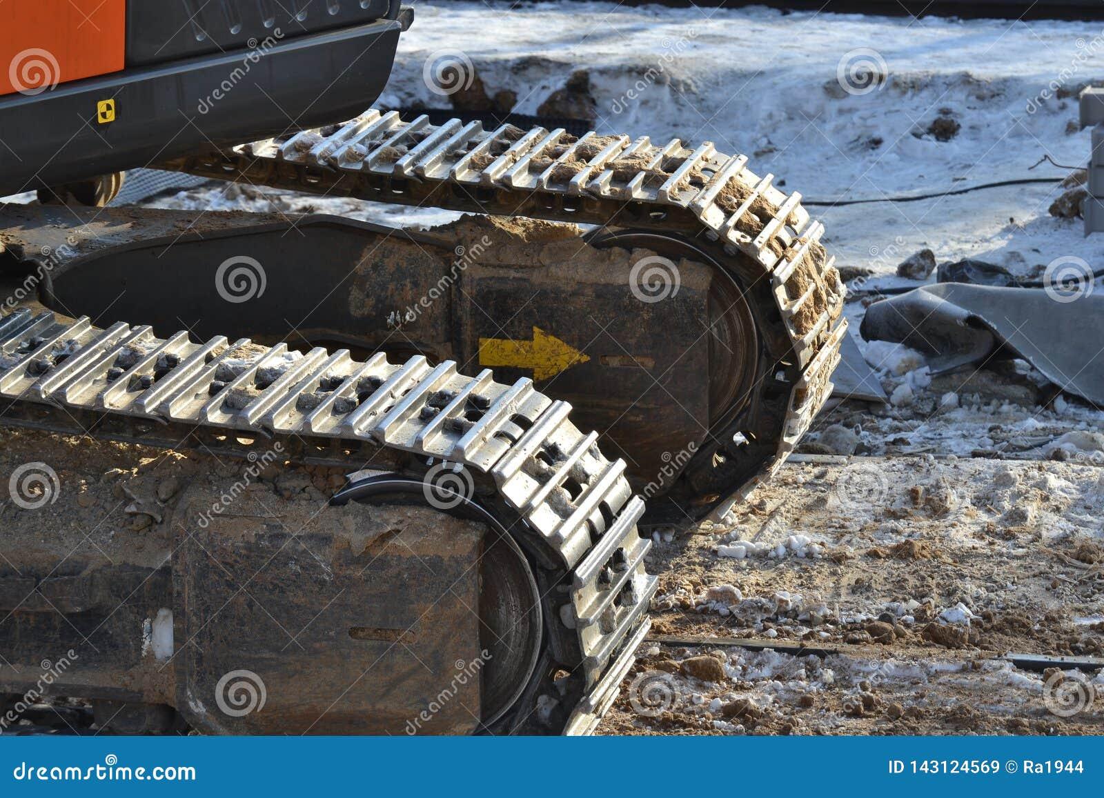 Следы крупного плана непрерывные или отслеживаемое колесо экскаватора или backhoe на поле почвы