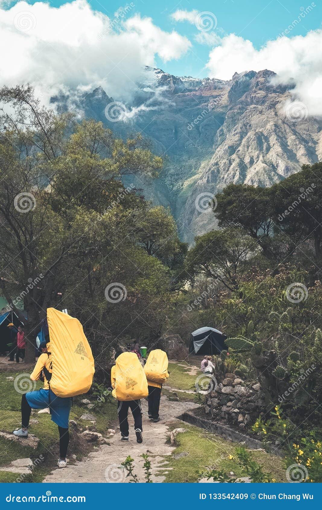 """След Inca, Перу: 11-ое августа 2018: Портеры Inca носят багаж туристов """"и располагаясь лагерем объекты во время трека следа Inca"""