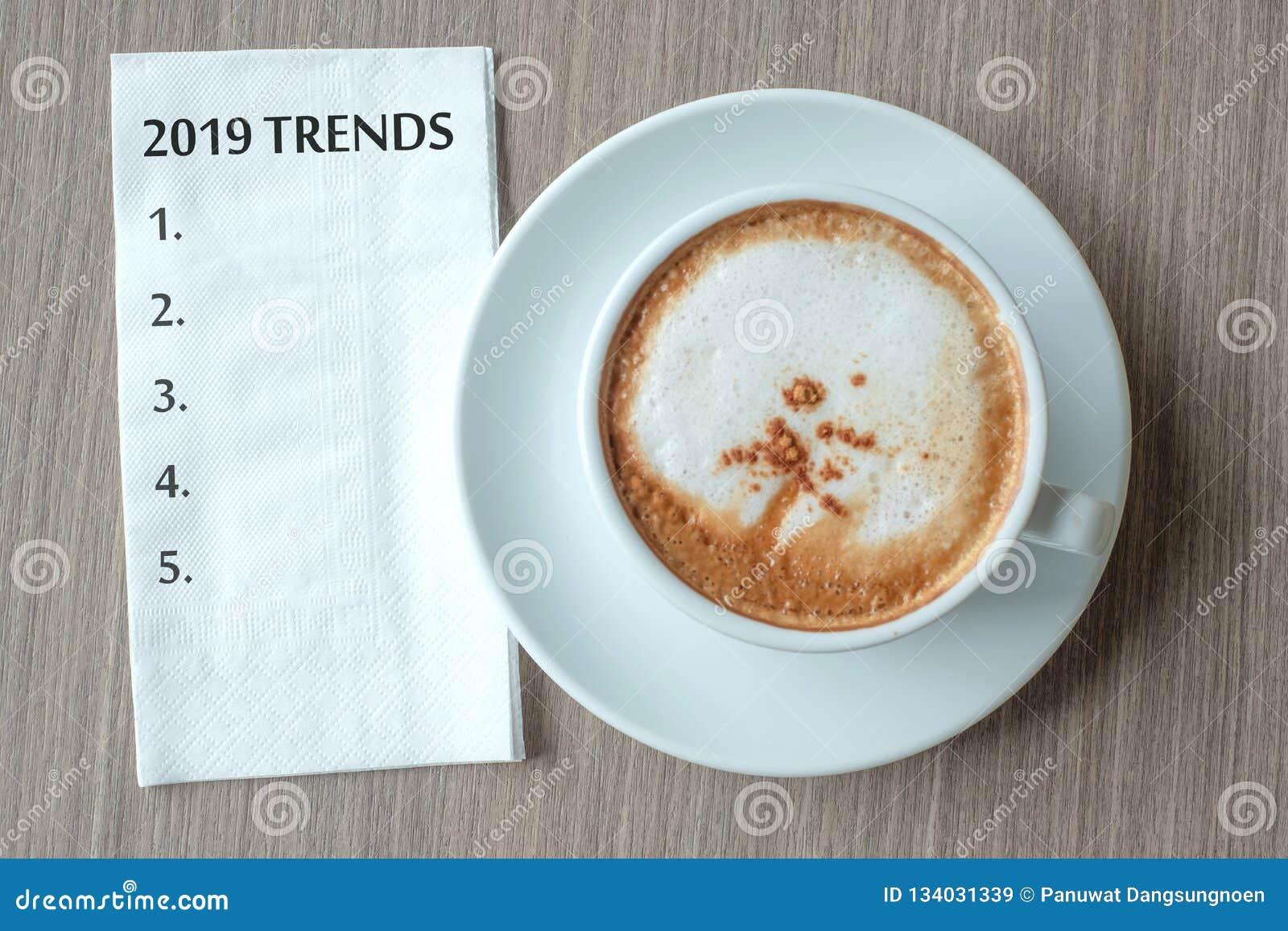 Слово 2019 ТЕНДЕНЦИЙ с горячей кофейной чашкой капучино на предпосылке таблицы на утре Начало Нового Года новое, разрешение, реше