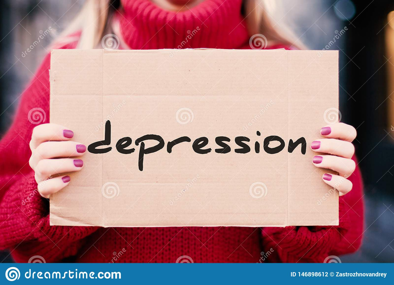 """Слово """"депрессия """"в руках девушки на улице, написанных на плите картона"""