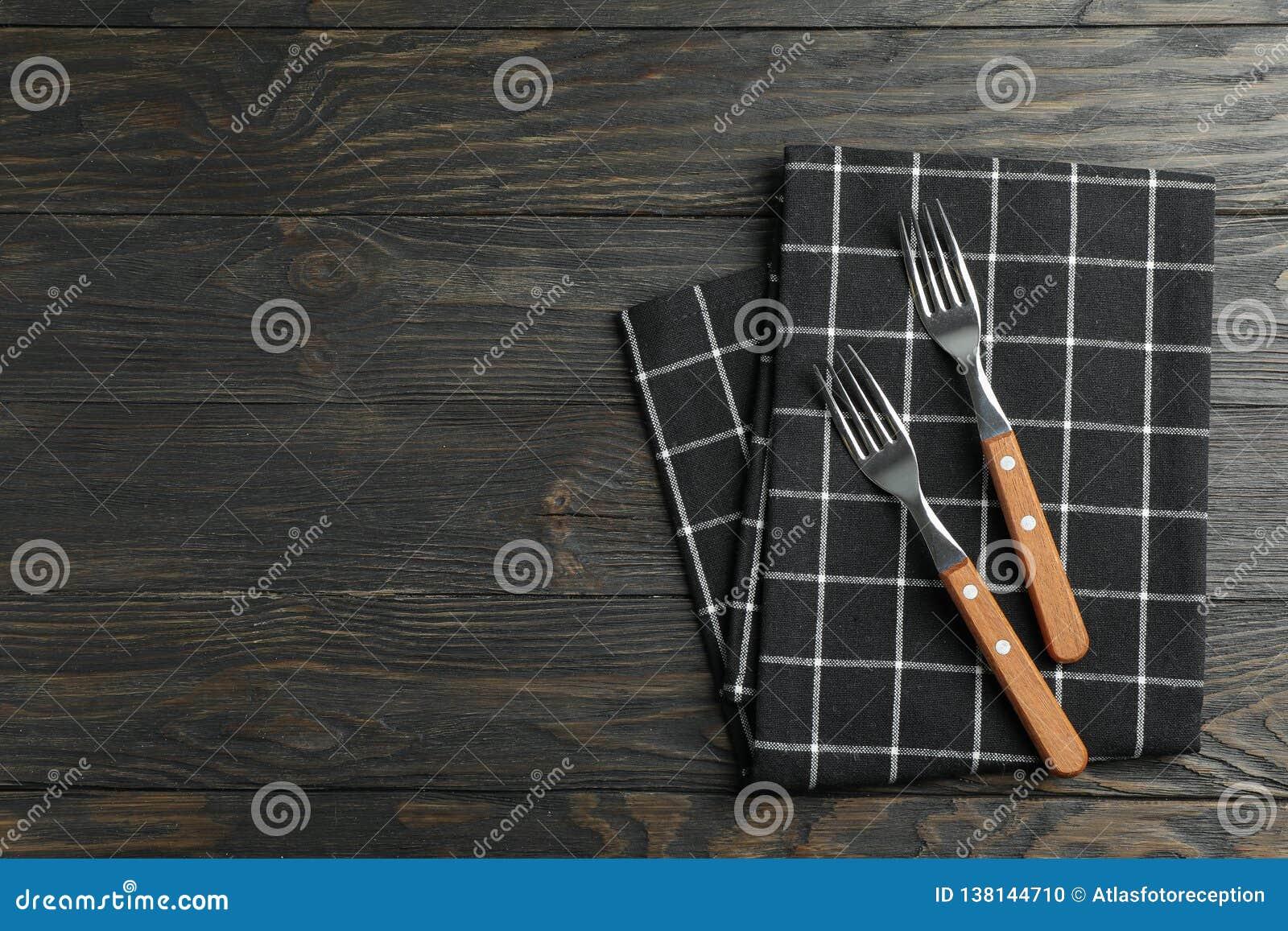 Сложенная салфетка ткани с вилками на деревянной предпосылке, взгляде сверху