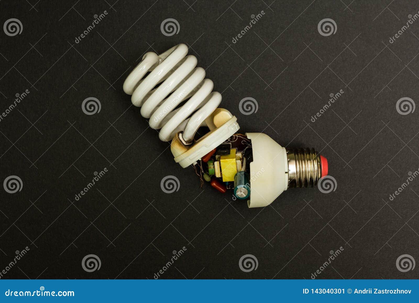 Сломленная люминесцентная лампа на черной предпосылке