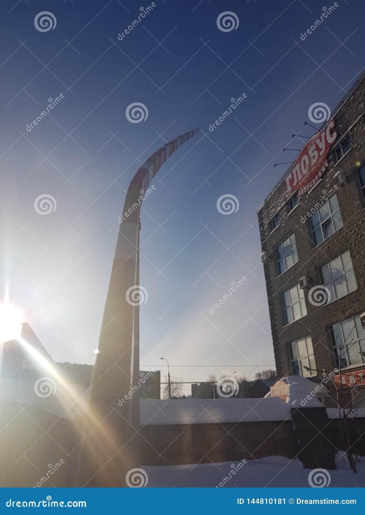 Сломленный изогнутый барьер против голубого неба и здания