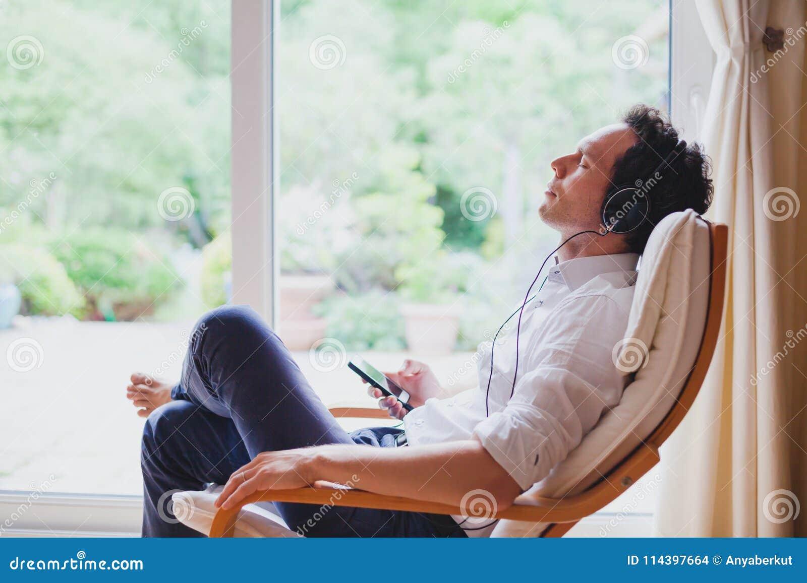 Слушая расслабляющая музыка дома, расслабленный человек в наушниках сидя в шезлонге