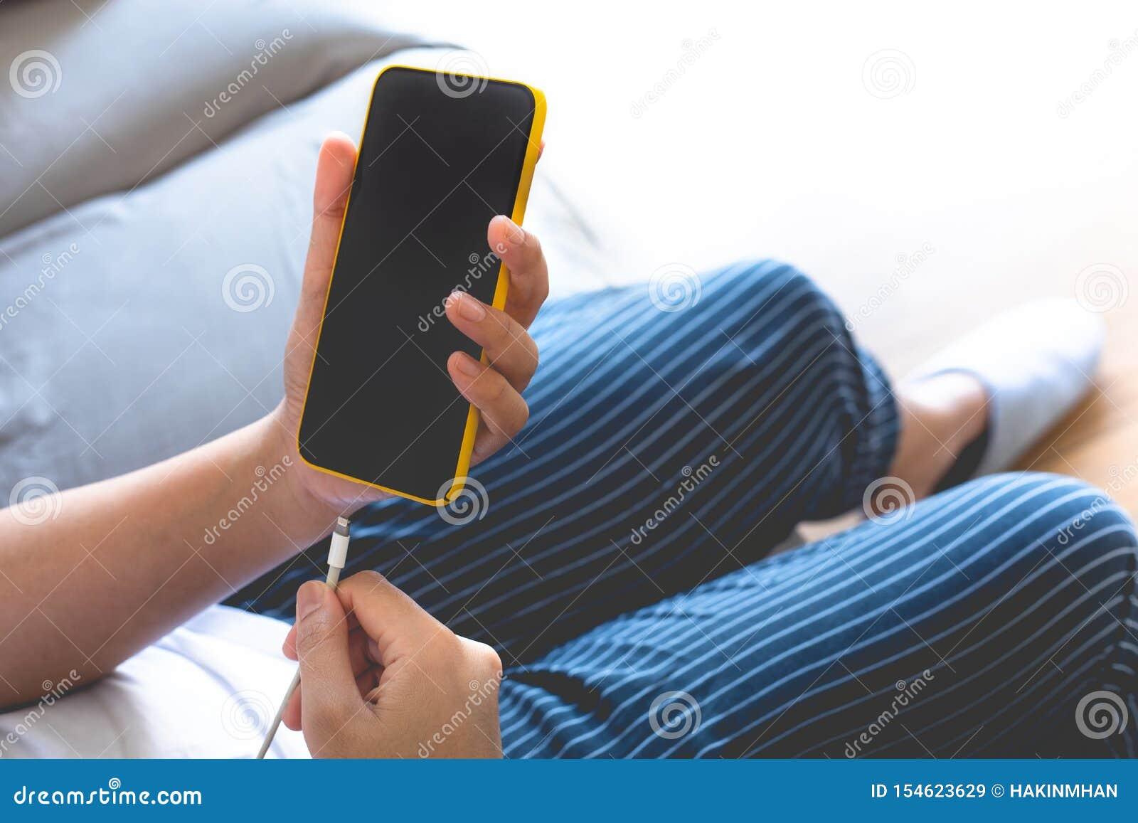 Смартфон женщины поручая банк энергии низкая батарея радиотехническая аппаратура