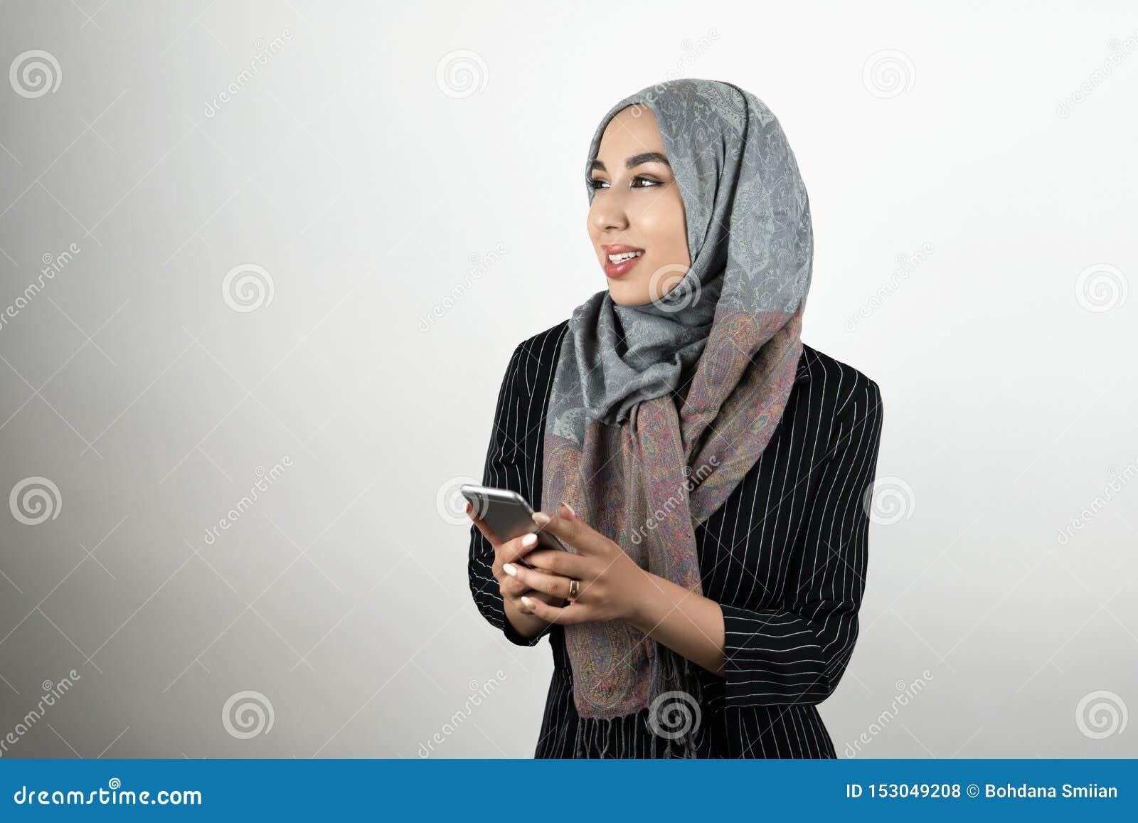 Смартфон удерживания головного платка hijab тюрбана молодой красивой мусульманской женщины нося в ее предпосылке изолированной ру