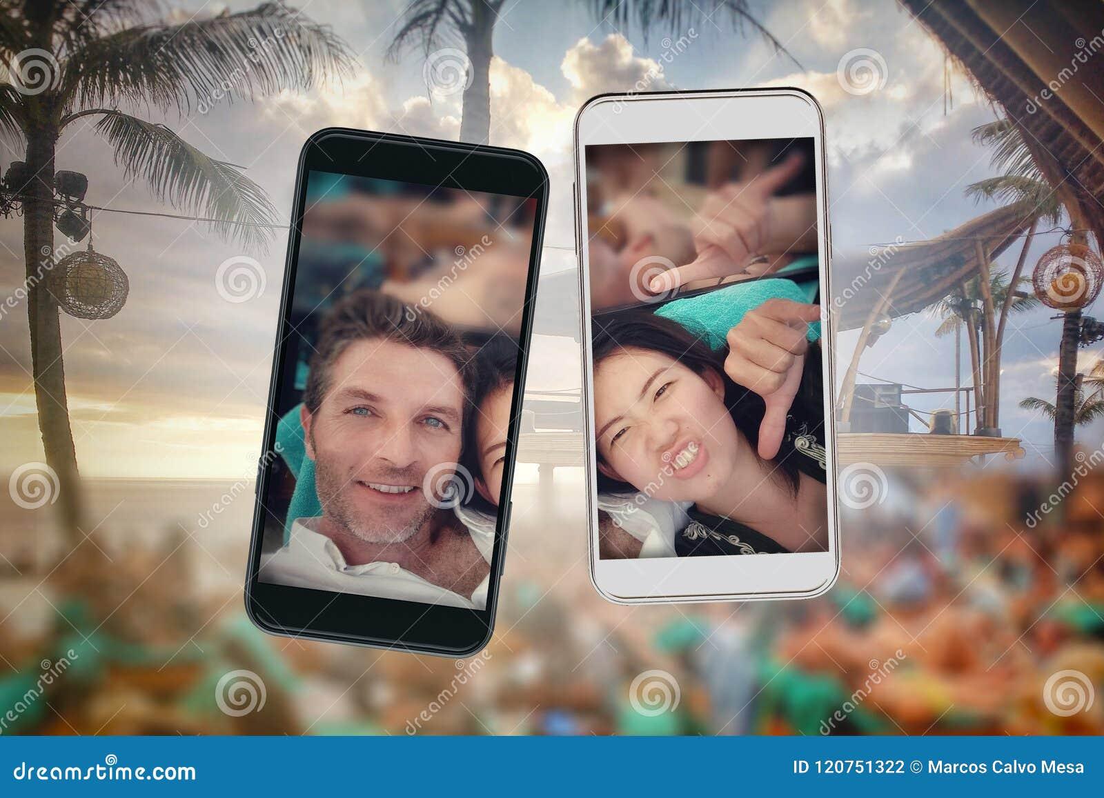 Смесь молодых пар красивой и счастливой смешанной этничности азиатских и кавказских и мобильных телефонов в pic selfie влюбленнос