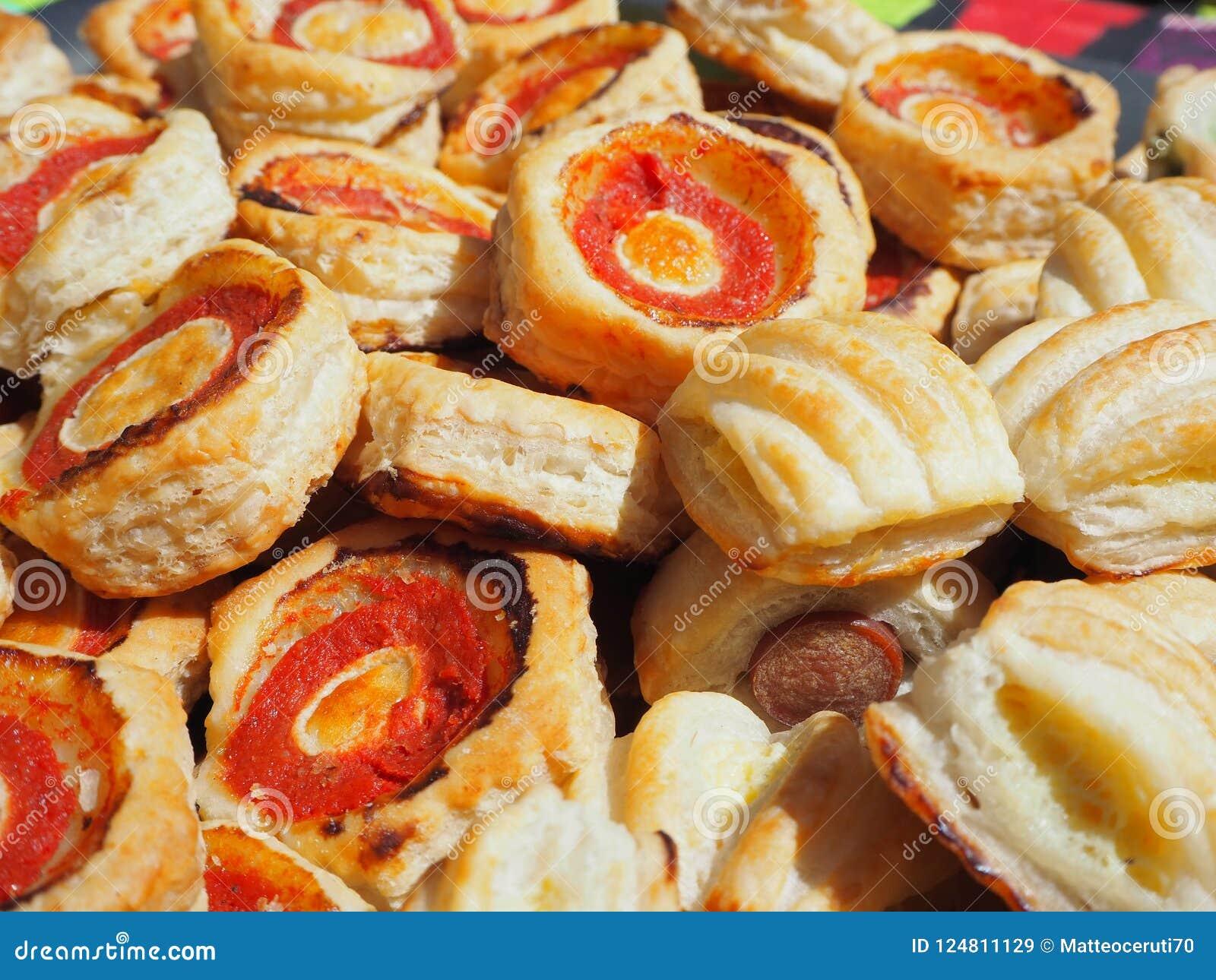 Смешивание очень вкусных закусок и малых пицц сделанных из печенья слойки