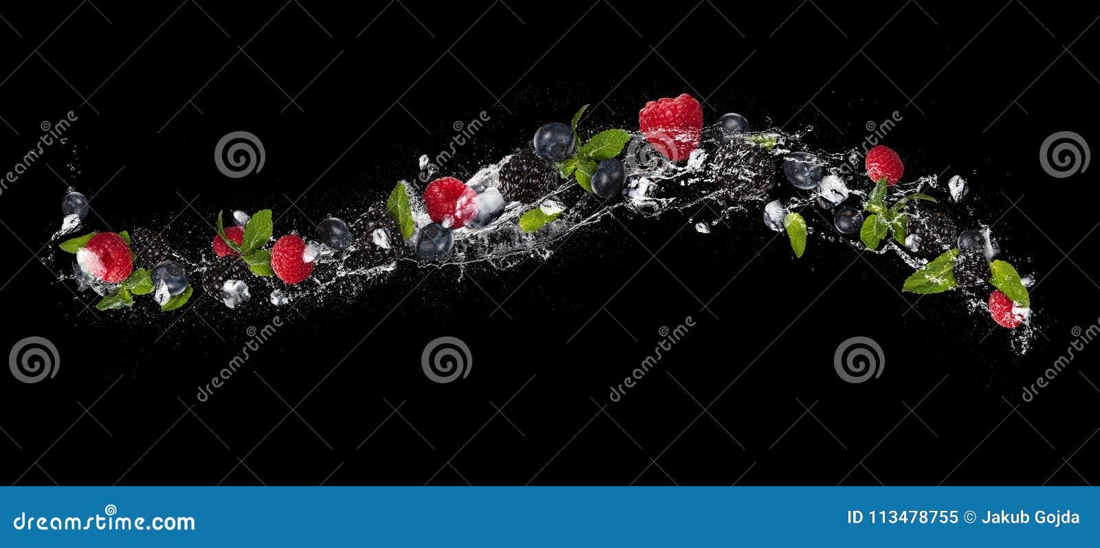 Смешивание плодоовощ ягоды в выплеске воды, изолированное на черной предпосылке