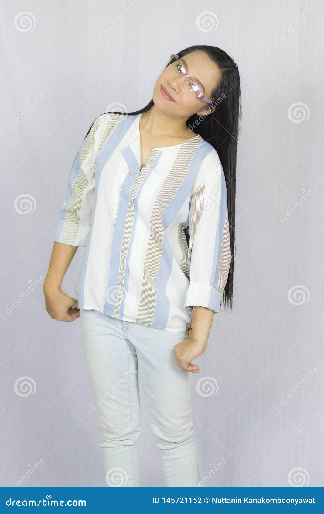 Смешная азиатская женщина в стеклах представляя счастливую улыбку изолированная на серой предпосылке