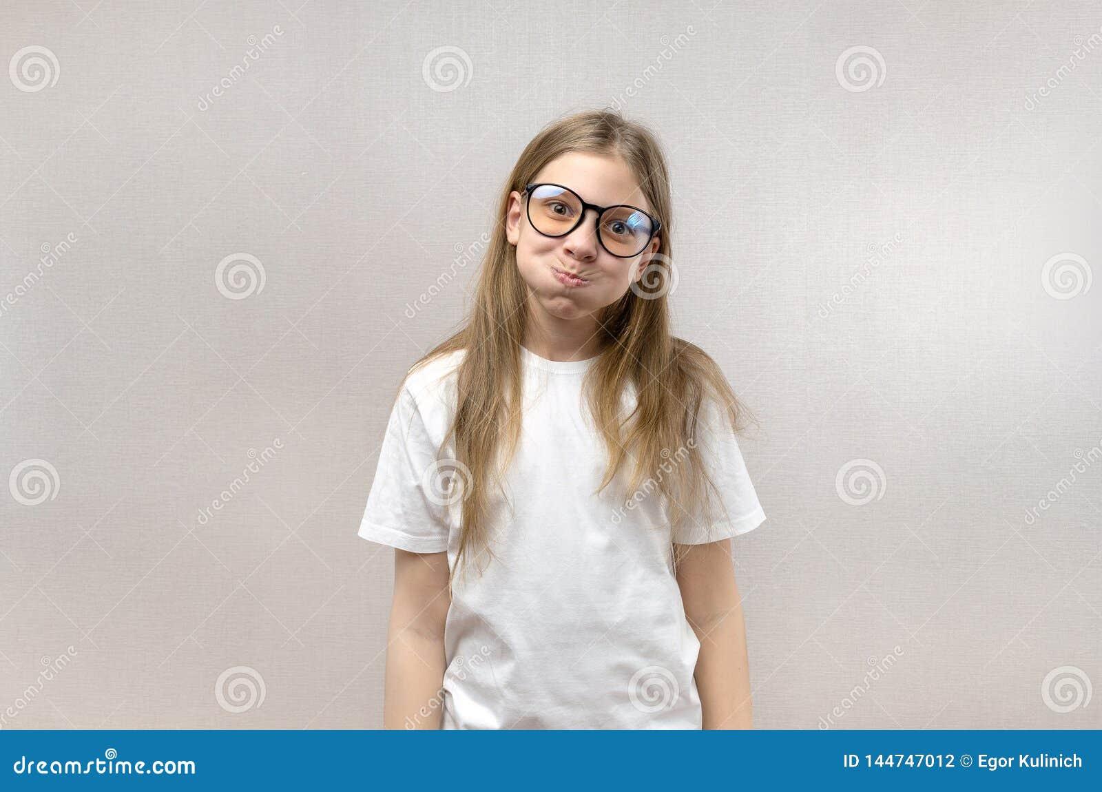 Смешная белокурая девушка в стеклах корчась ее сторона, передразнивающ, имеющ потеху :