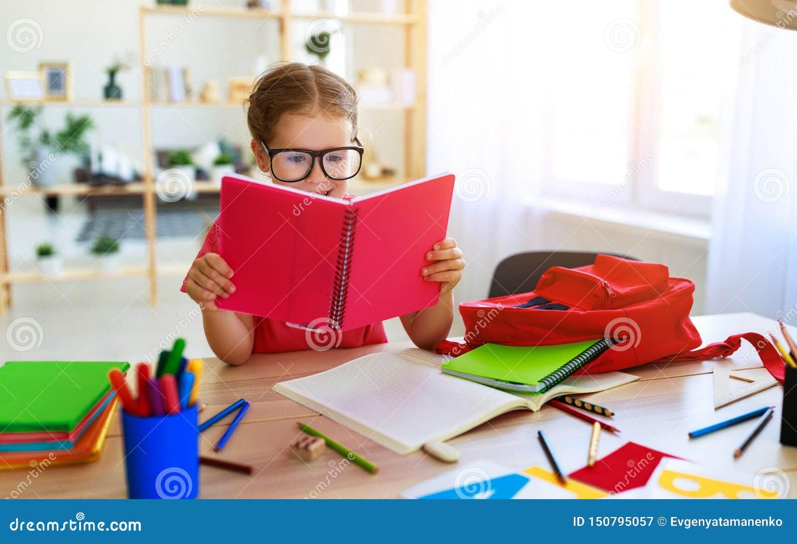 Смешная девушка ребенка делая сочинительство домашней работы и читая дома
