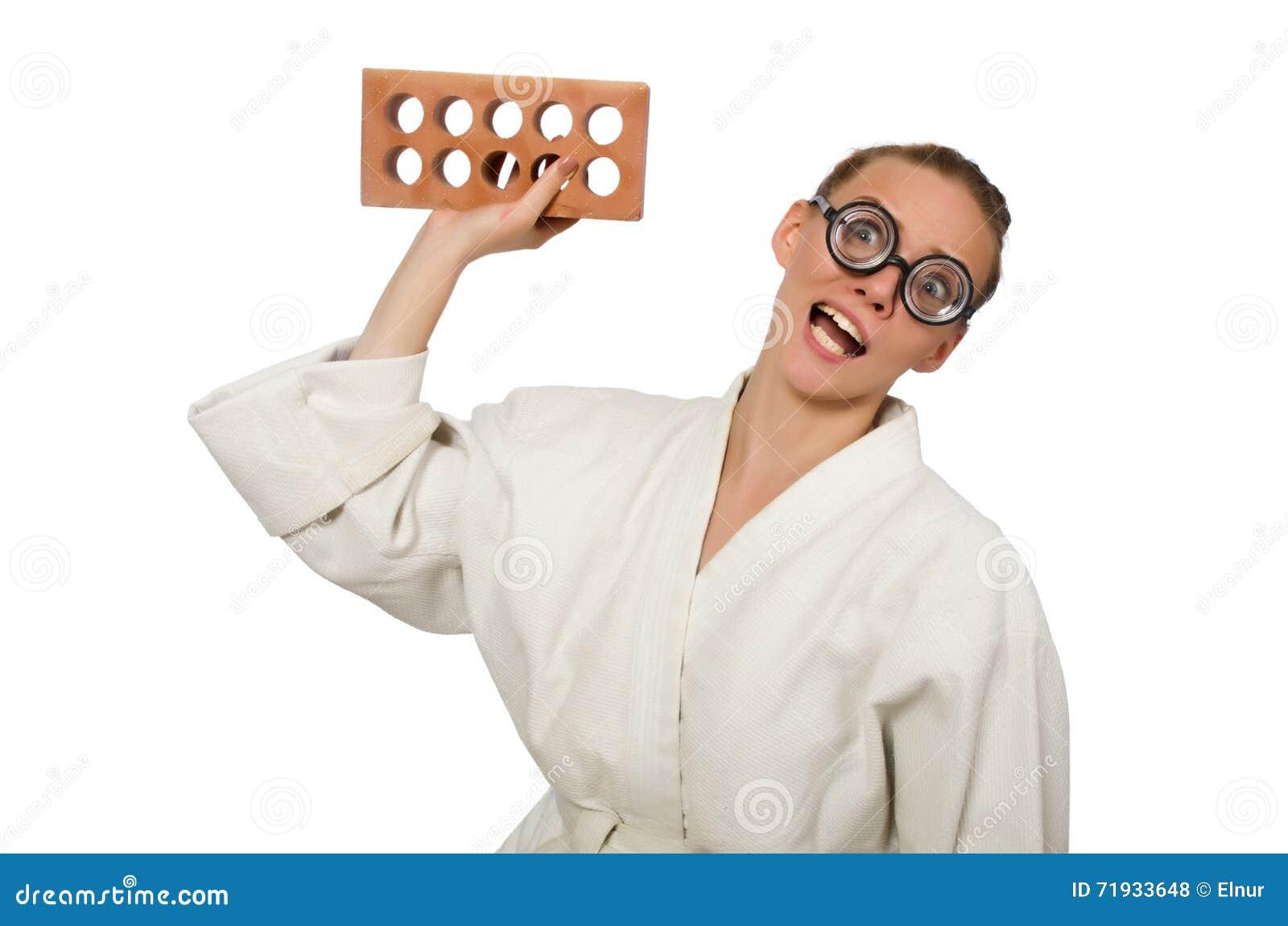Смешная женщина в кимоно с кирпичом на белизне