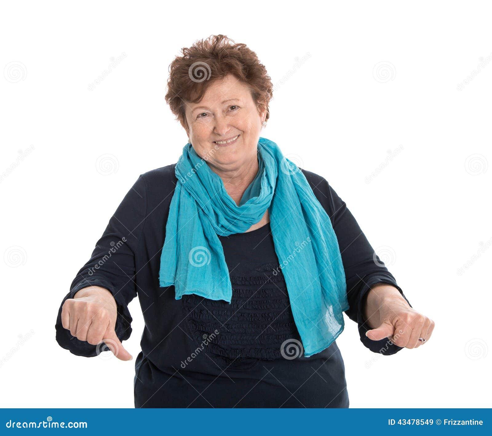 Смешная изолированная более старая дама в сини делая большие пальцы руки вниз показывать