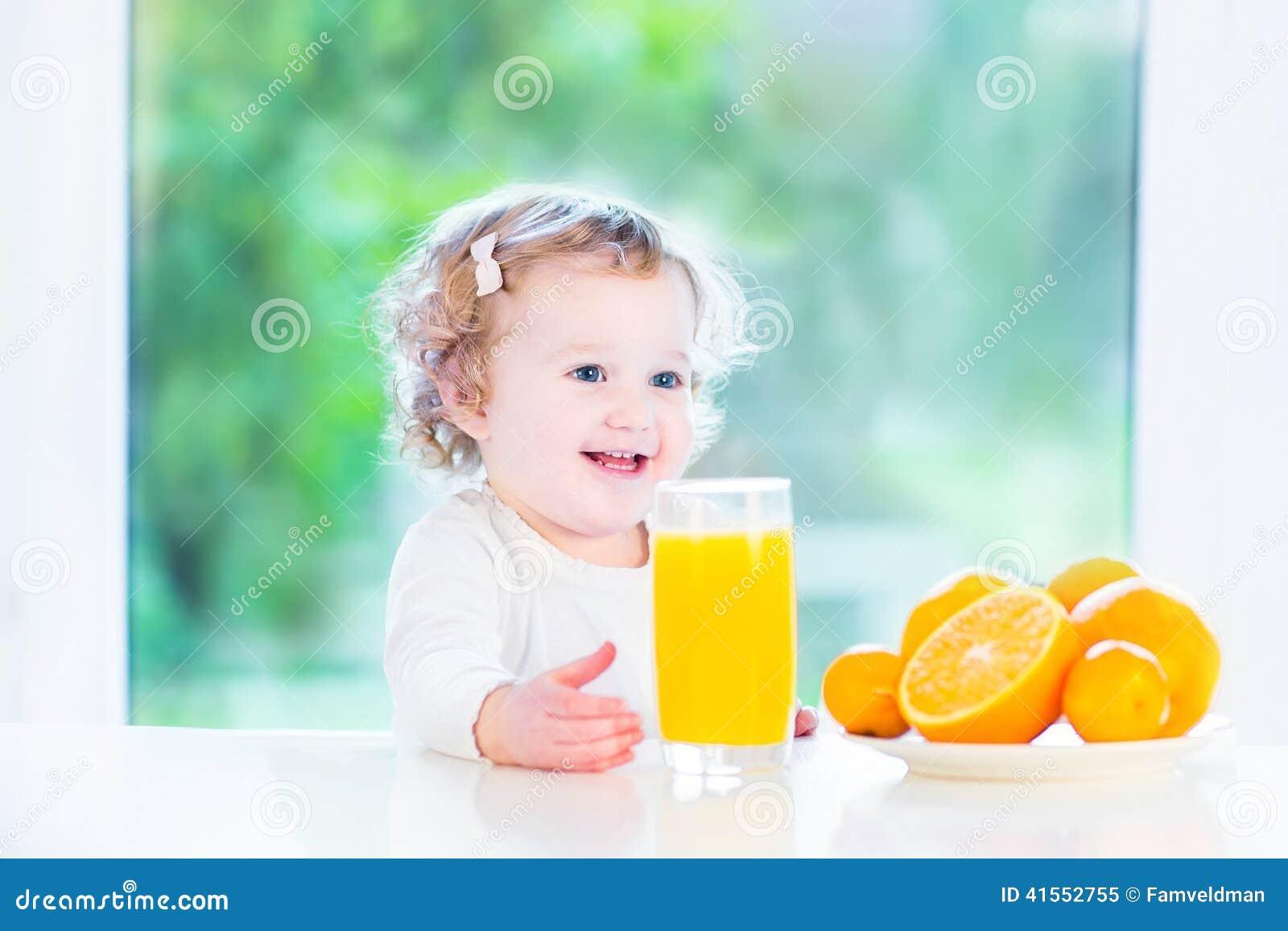 Смешная курчавая девушка малыша выпивая апельсиновый сок