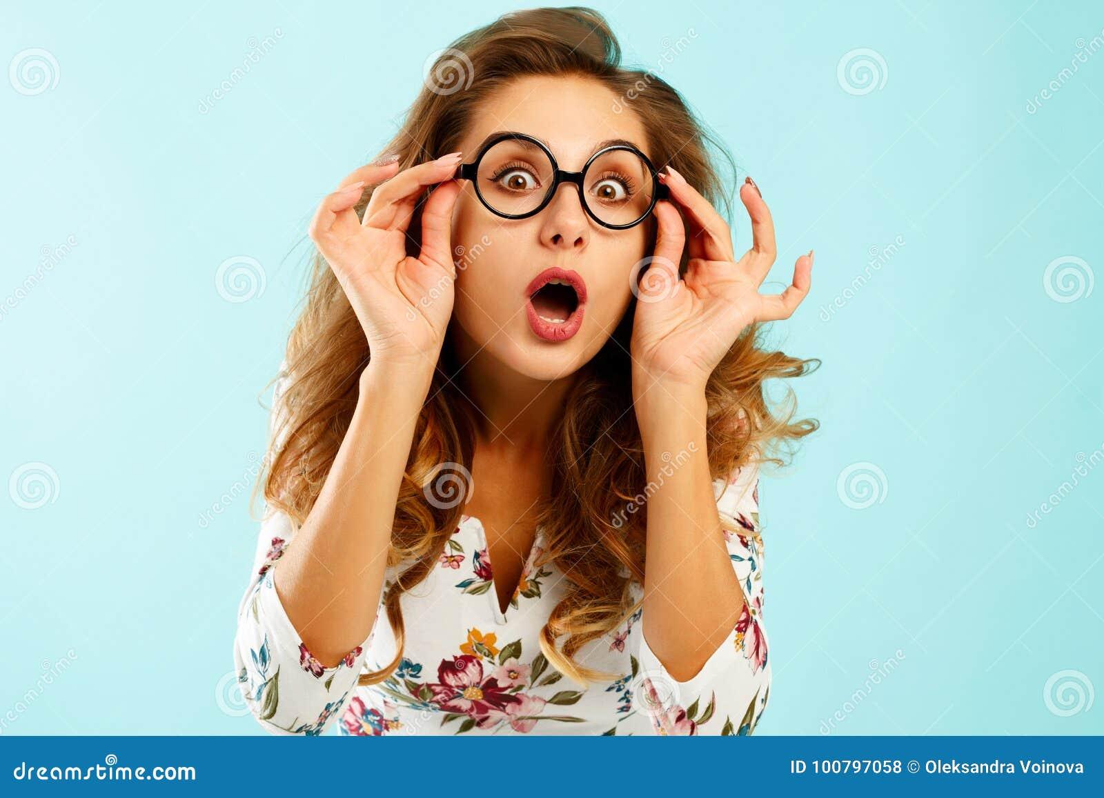 Смешная милая молодая женщина держа вокруг стекел над голубым backgro