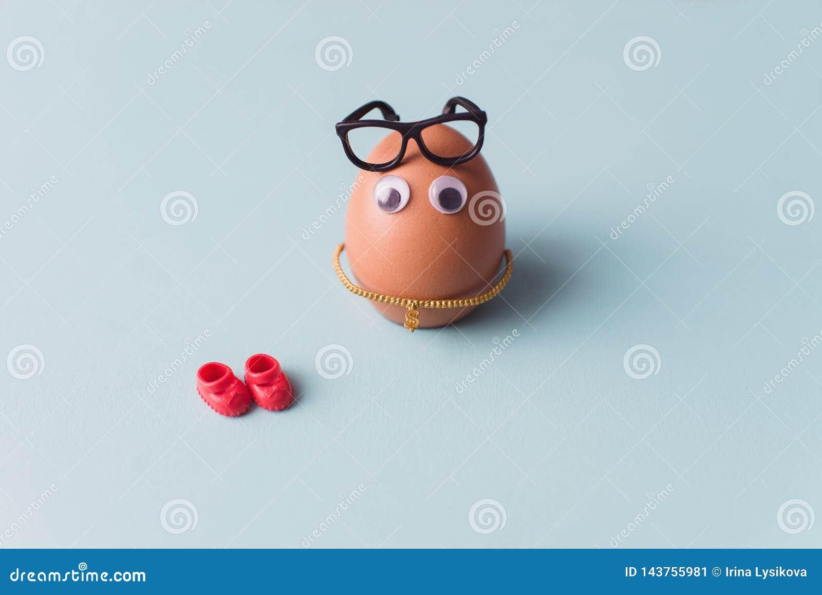 Смешное милое коричневое яйцо с черными стеклами и красными ботинками на голубой предпосылке