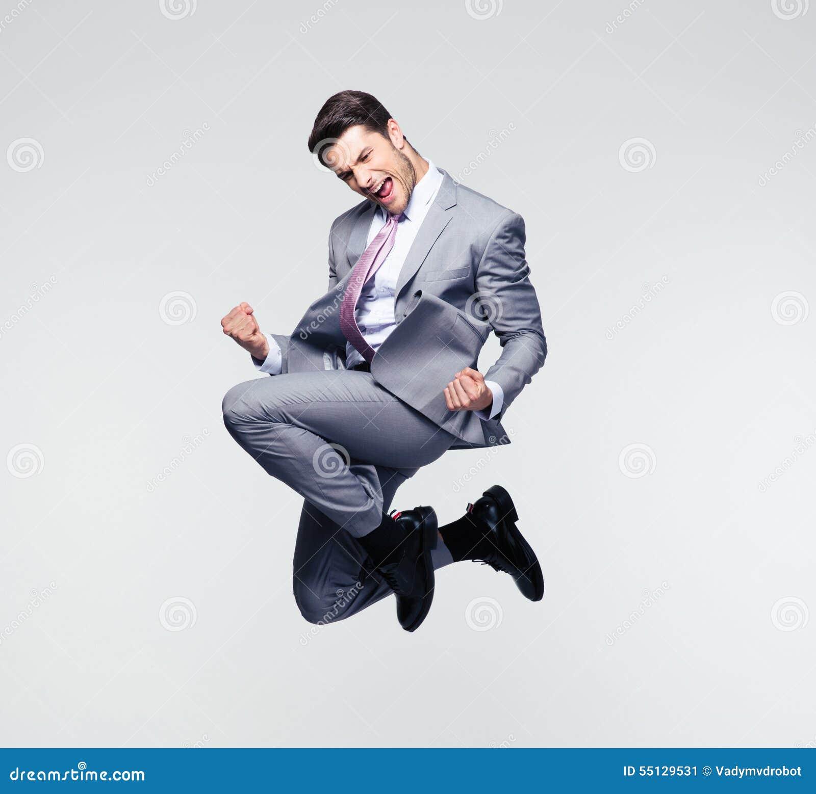 Смешной бизнесмен скача в воздух