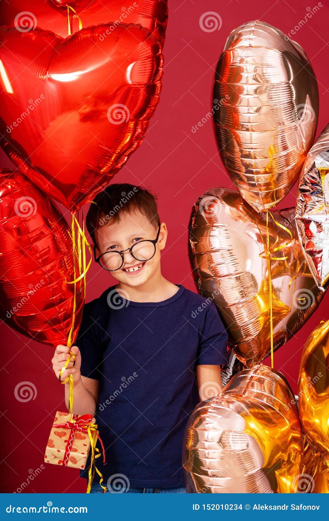 Смешной мальчик ребенк в стеклах, сердце другого цвета, воздушных шарах звезды на день Святого Валентина или дне рождения на крас