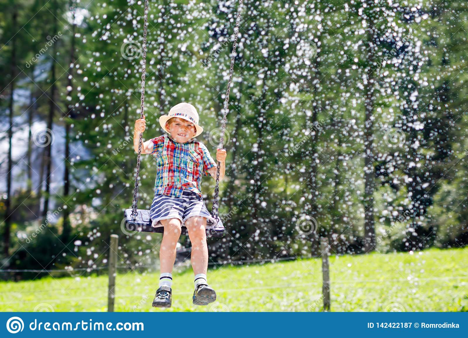 Смешной мальчик ребенк имея потеху при цепное качание на внешней спортивной площадке пока был влажными брызнутое с водой ребенок