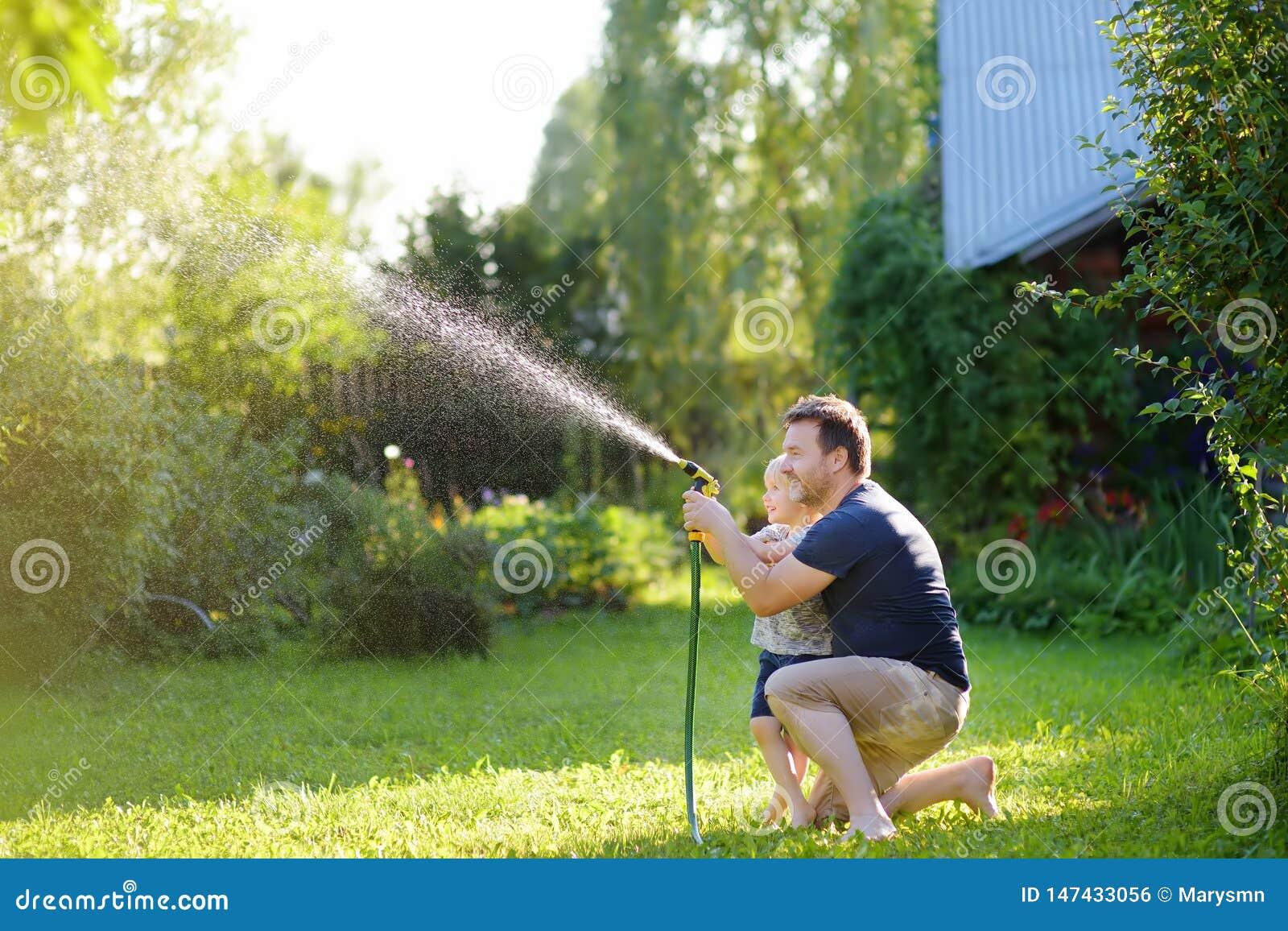 Смешной мальчик с его отцом играя со шлангом сада в солнечной задворк Ребенок Preschooler имея потеху с брызгами воды