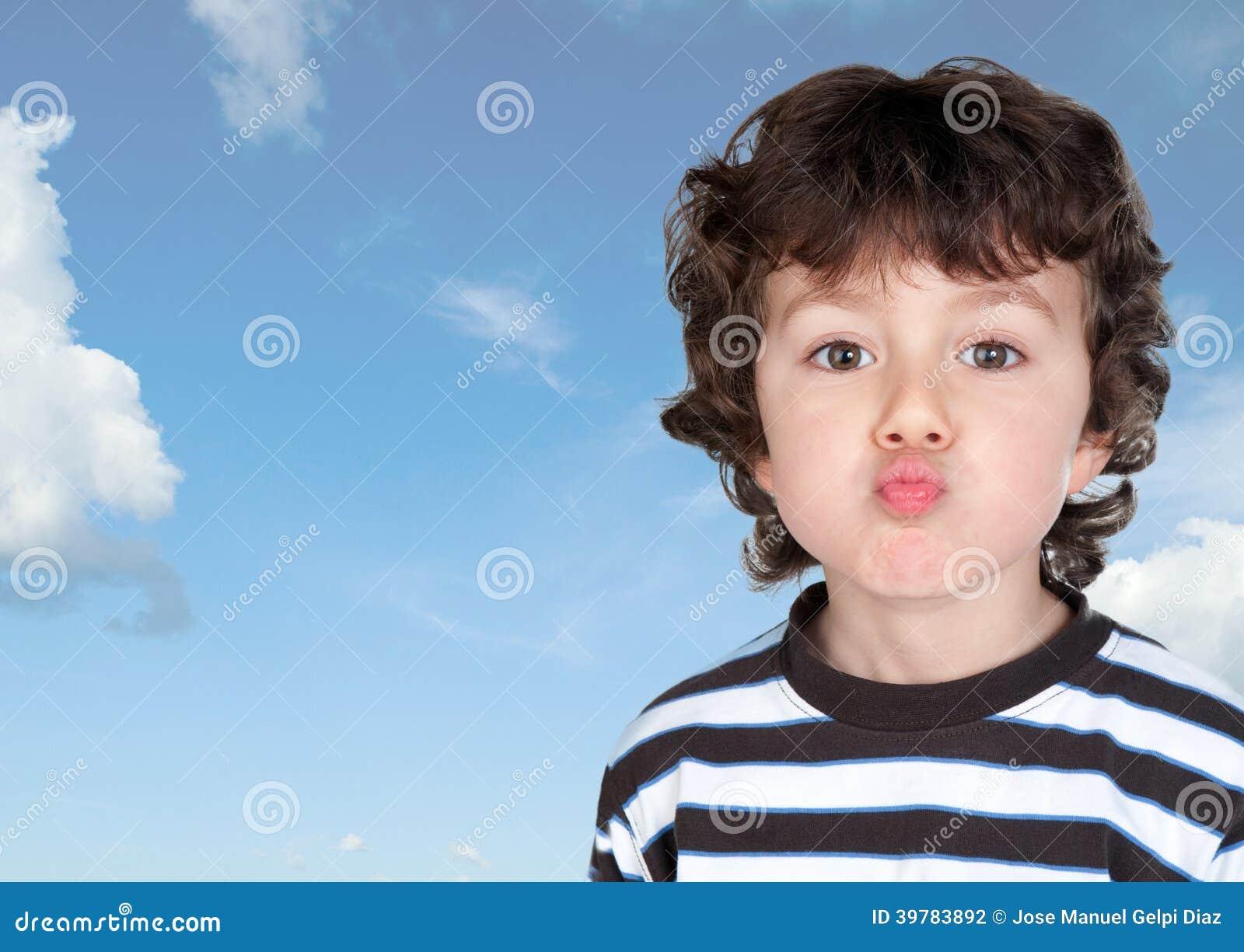 Смешной ребенок делая гримасу бросая поцелуй