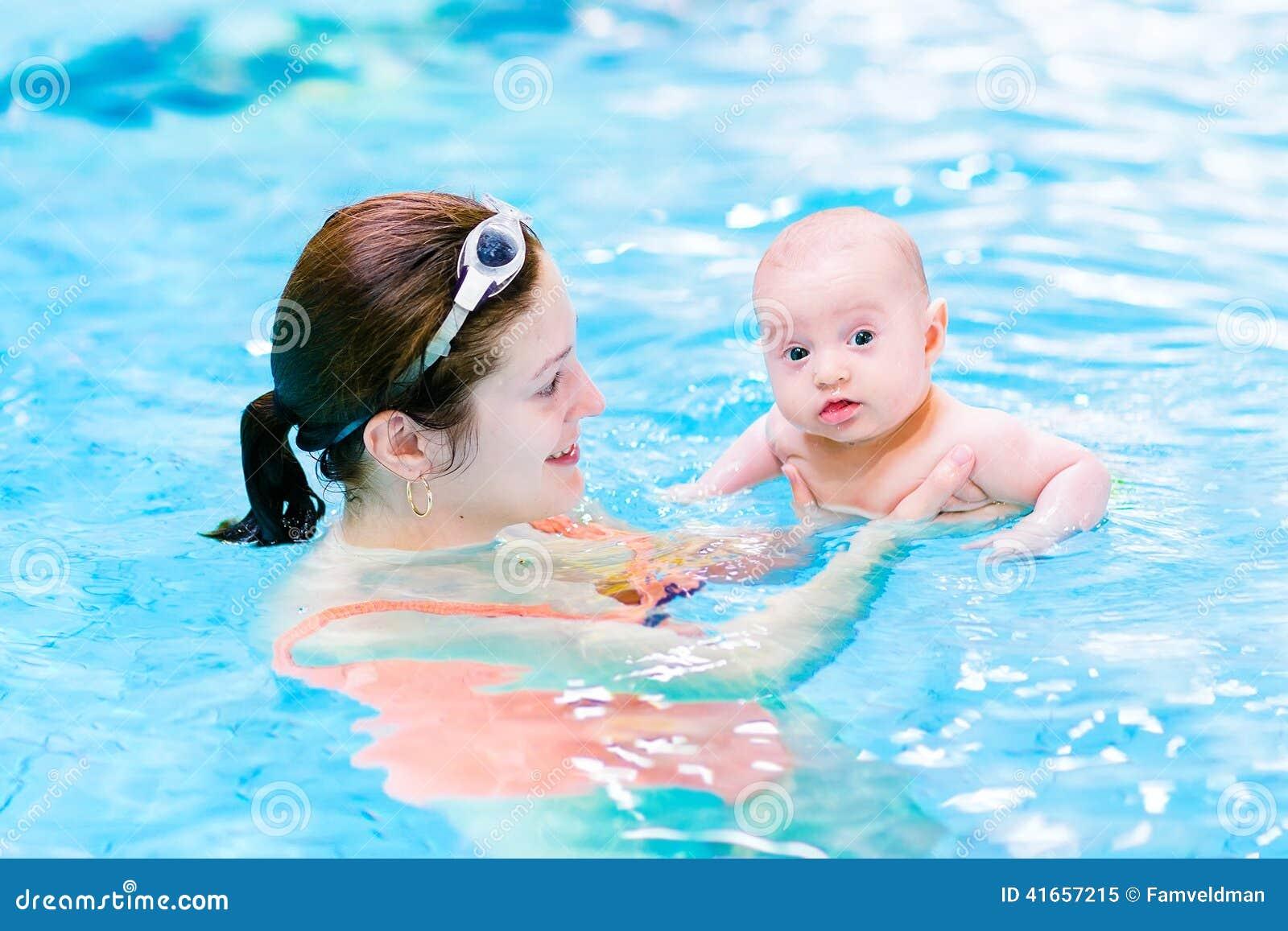 Смешной ребёнок в бассейне с его матерью