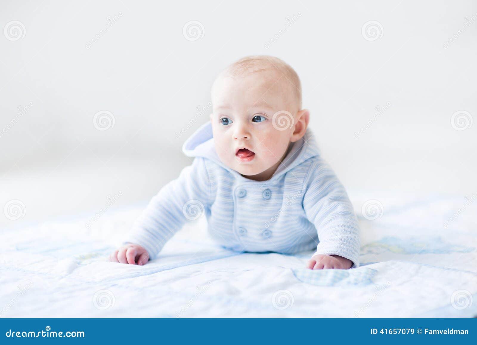 Смешной ребёнок играя на одеяле bue