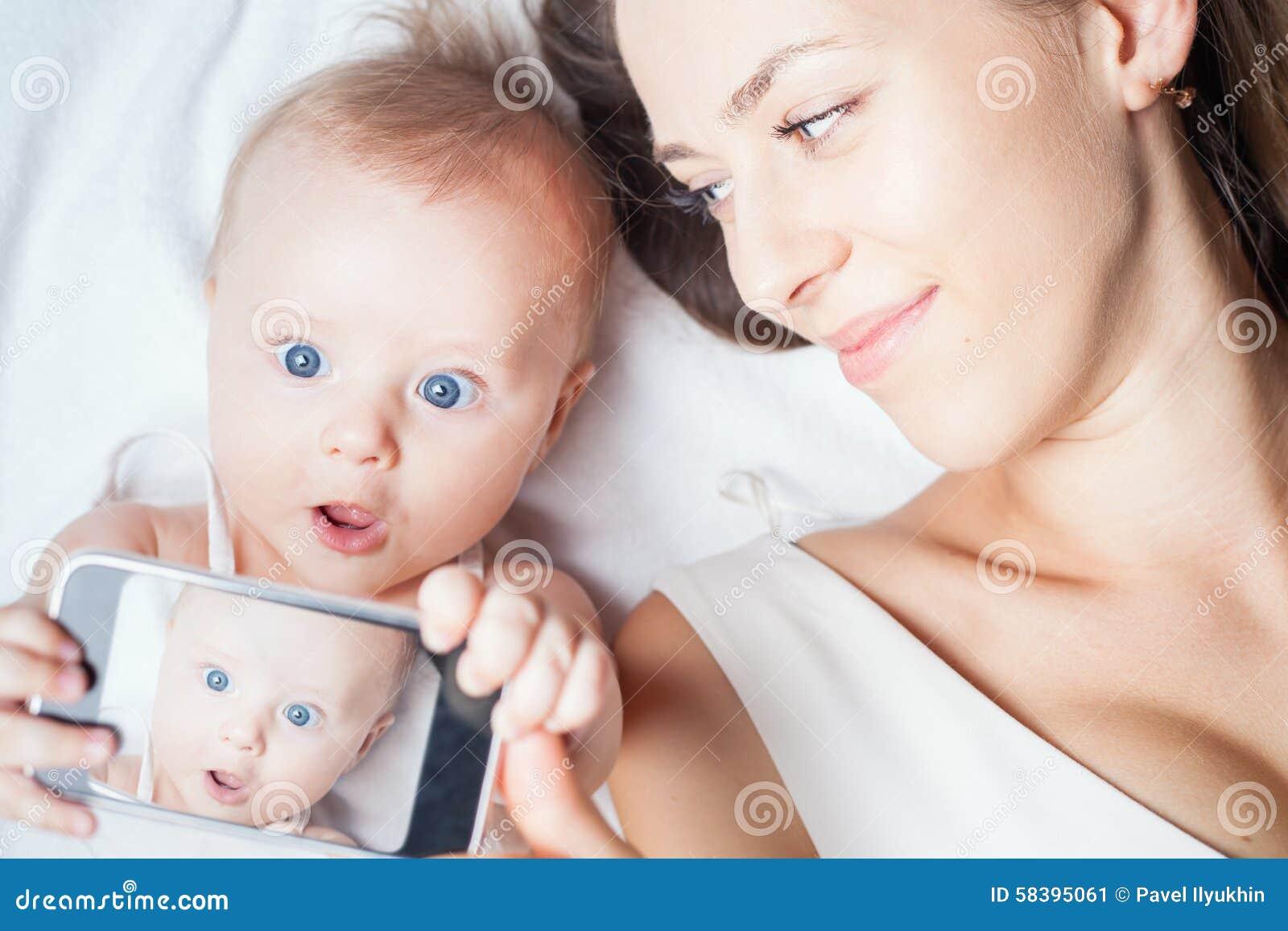 Смешной ребёнок с мамой делает selfie на мобильном телефоне
