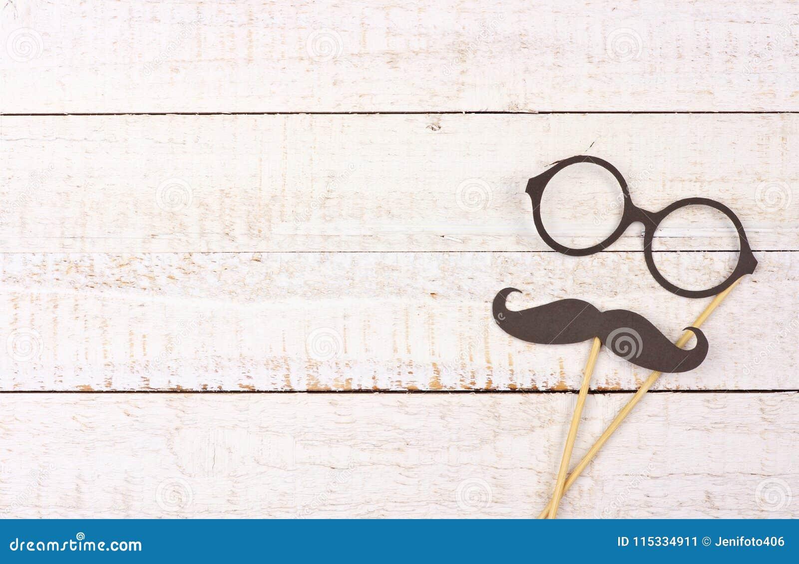 Смешной усик и стекла на ручках против белой древесины