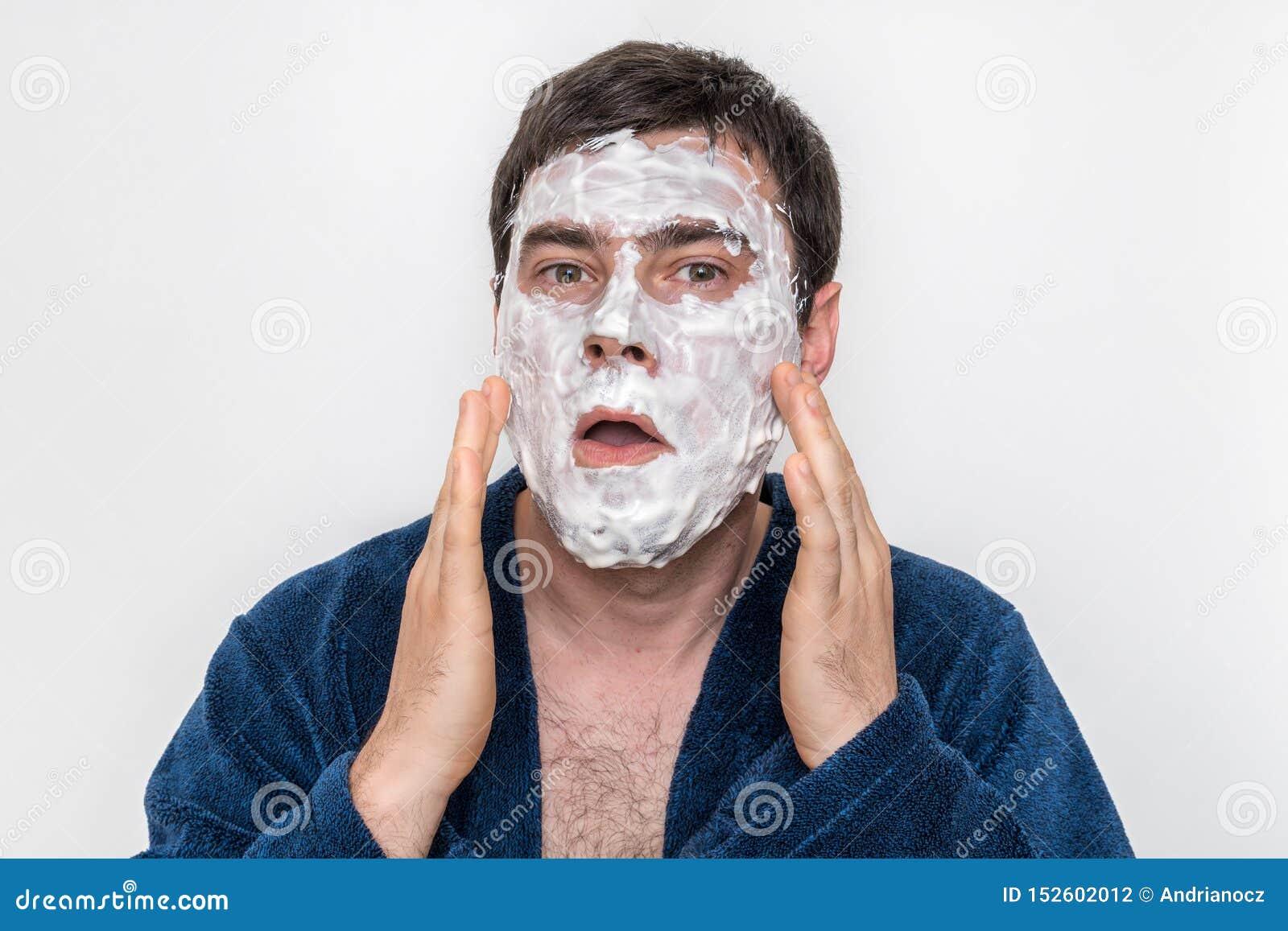 Смешной человек с естественной белой маской сливк на его стороне