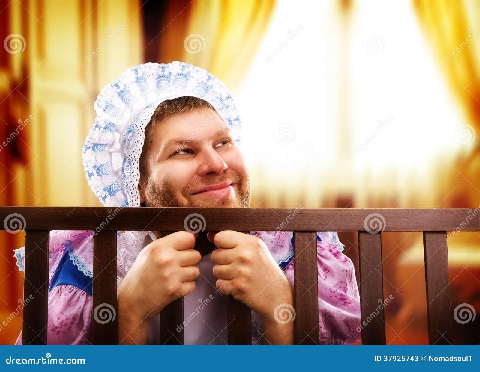 Смешной человек в playpen смотря вне