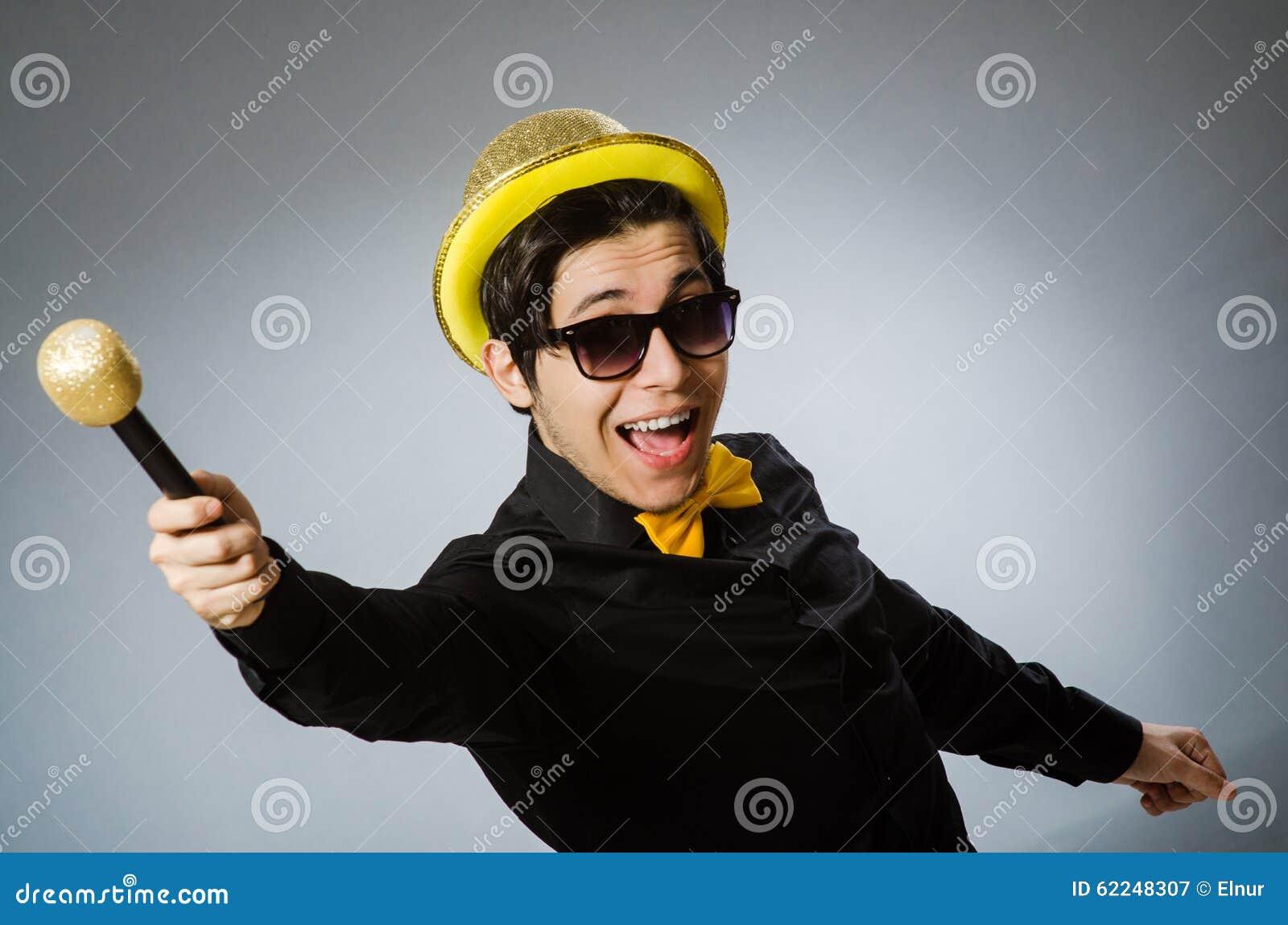 Смешной человек с mic в концепции караоке