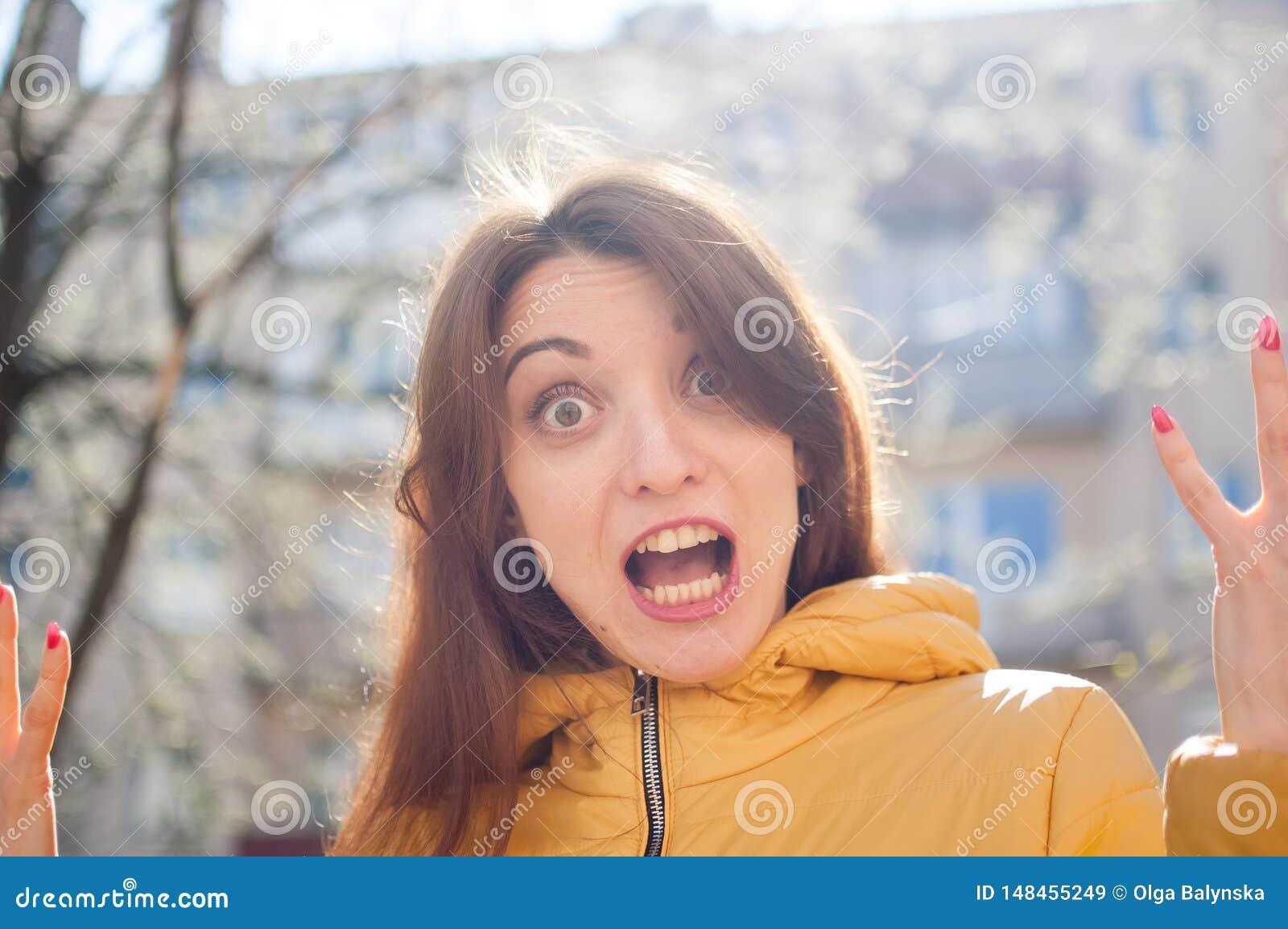 Смешной эмоциональный женский портрет молодого брюнета в яркой желтой куртке смотря камеру с невероятным ударом