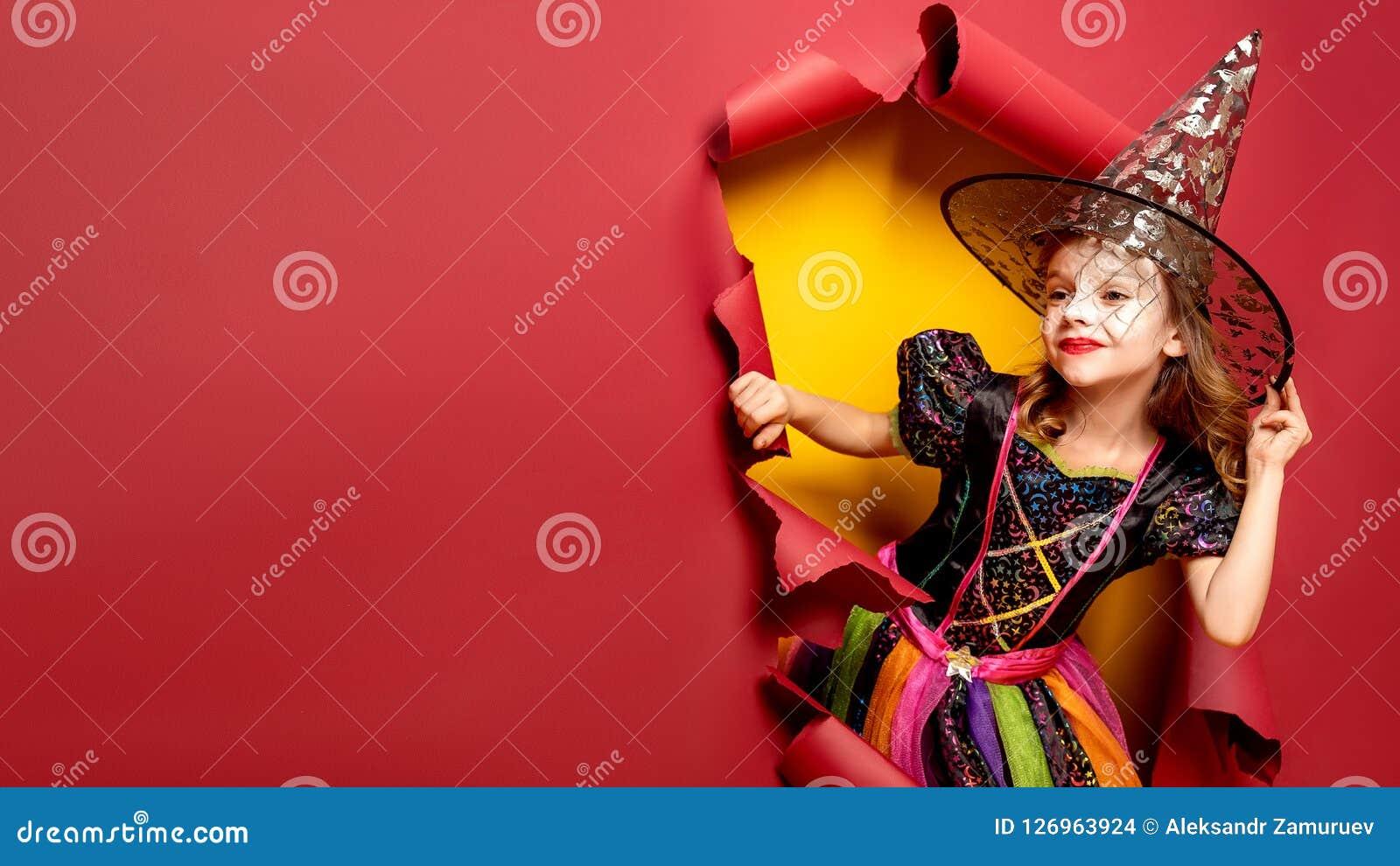 Смеясь над смешная девушка ребенка в костюме ведьмы в хеллоуине