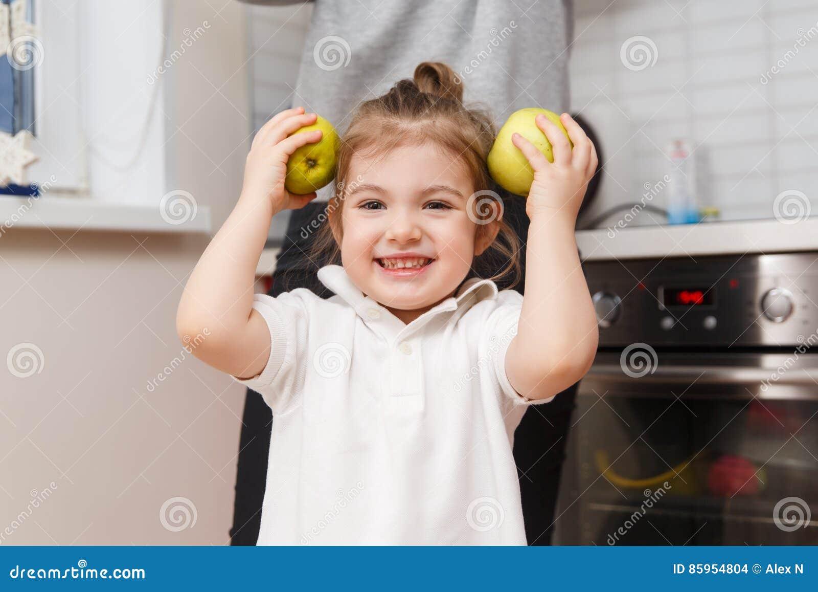 Смеясь над маленькая девочка с яблоками
