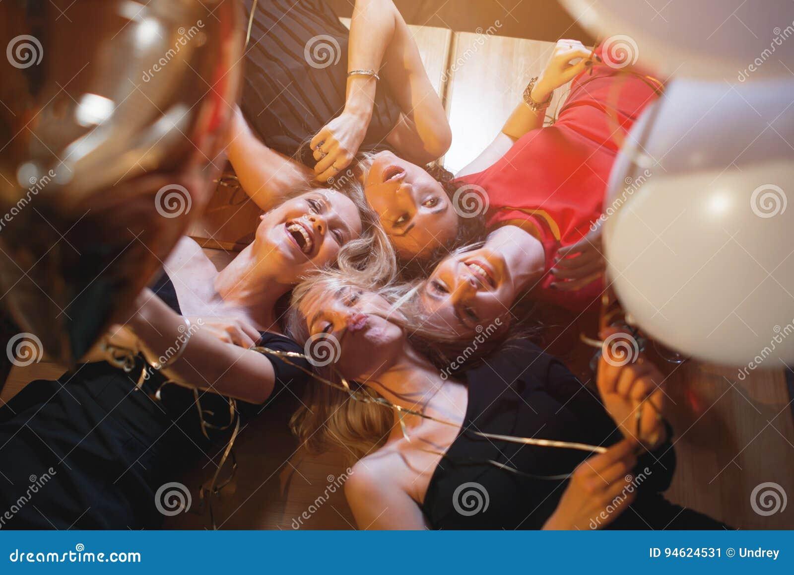 Смеясь над молодые женщины смотря вниз в камеру держа воздушные шары имея партию