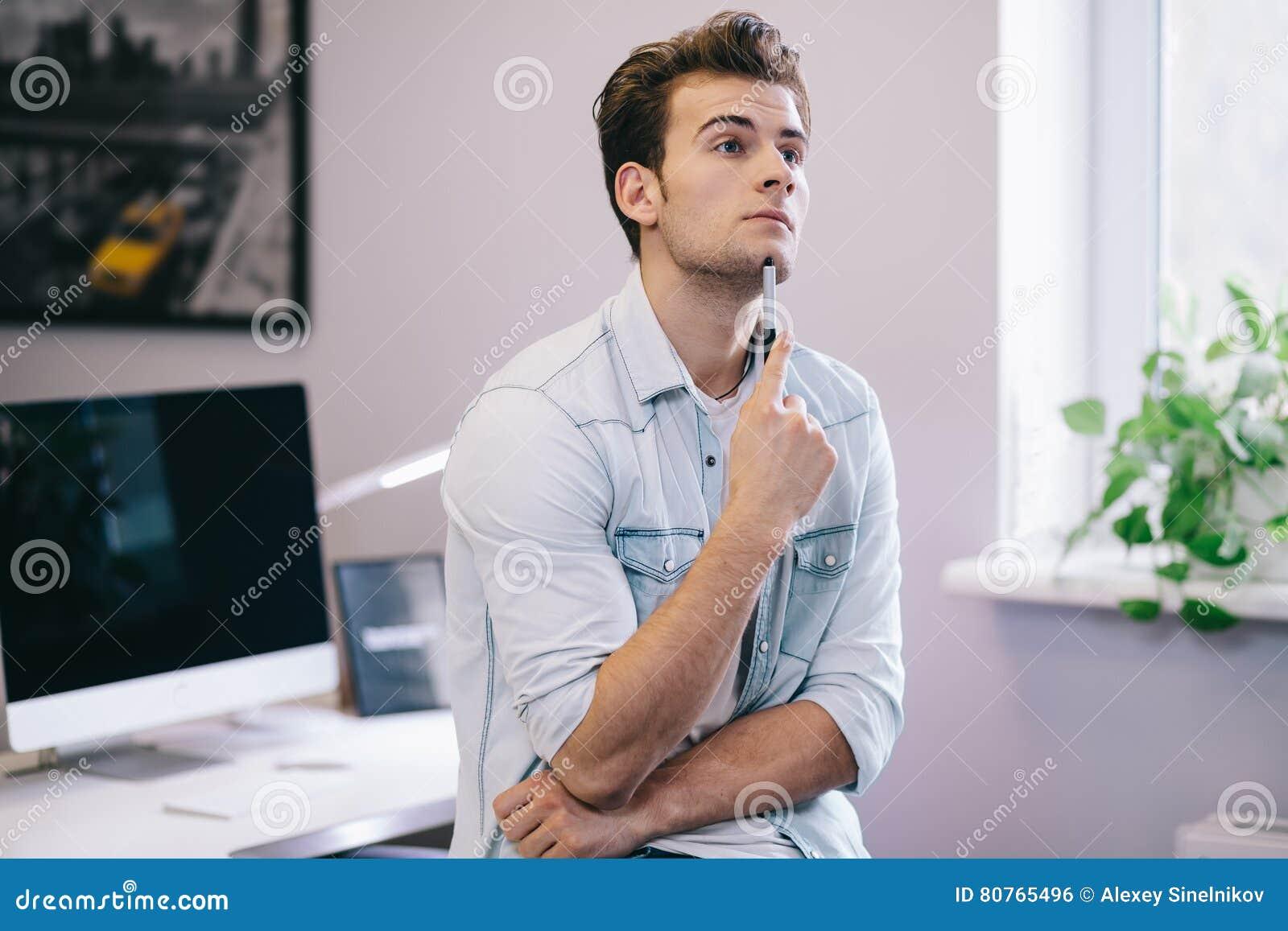 Смотреть от деятеля в офисе Стильный дизайнер на работе Сфокусированный на его работе