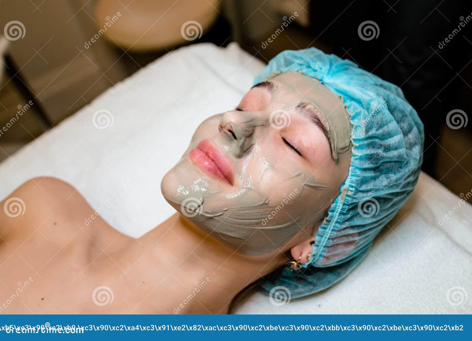 Смотрите на маску шелушения, косметику курорта, skincare Женщина получая лицевую заботу beautician на салоне курорта