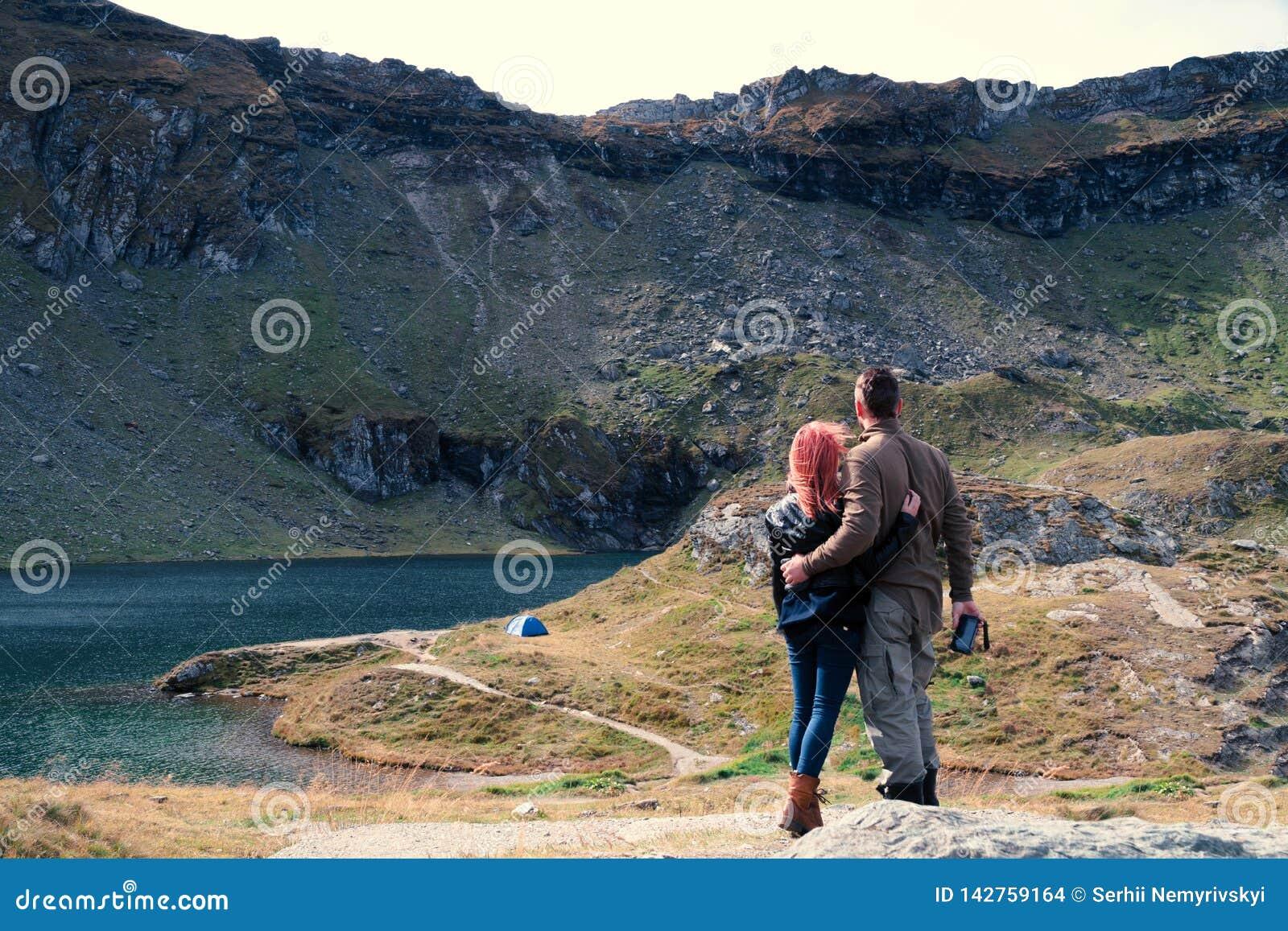 Смотрят, что дистанцируют пары на верхней части горы, озере Lac Balea Космос для текста, каникул шатра перемещения располагаясь л